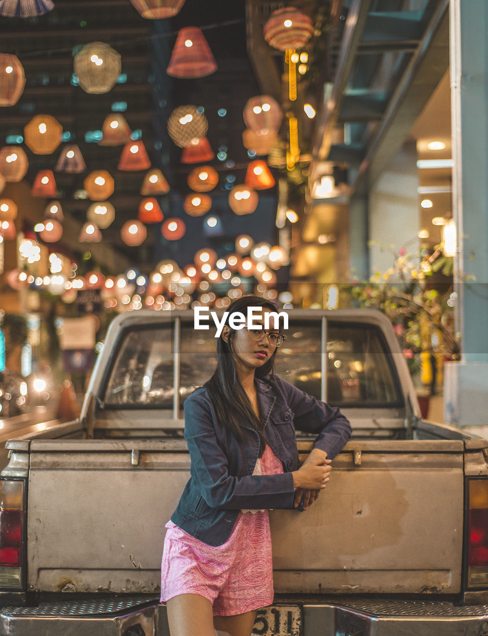 Portrait of teenage girl standing against pick-up truck at illuminated street