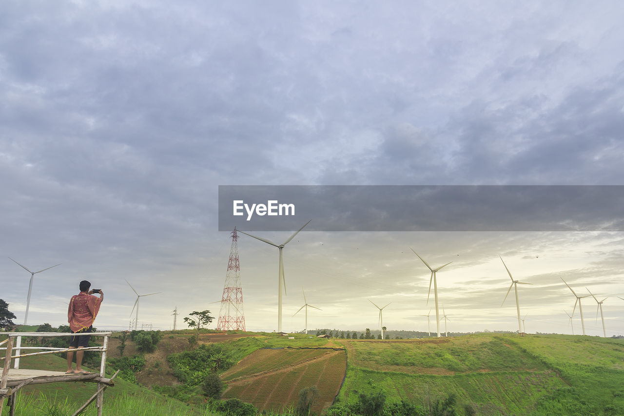 renewable energy, alternative energy, wind turbine, fuel and power generation, turbine, cloud - sky, wind power, environmental conservation, sky, environment, technology, nature, field, land, landscape, one person, real people, day, beauty in nature, scenics - nature, outdoors, sustainable resources