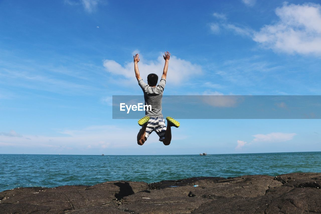Man Jumping Over Sea Against Blue Sky
