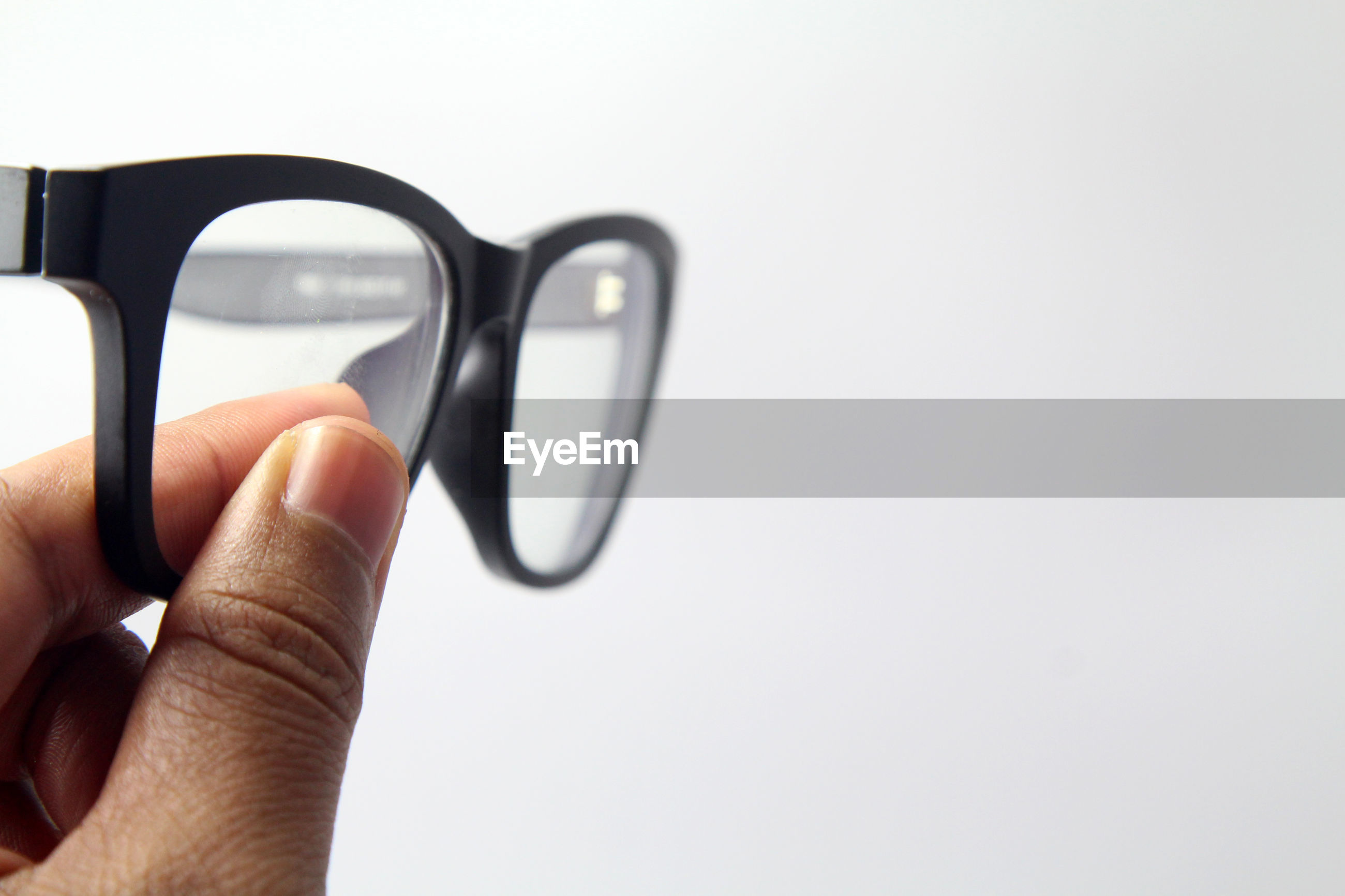 Cropped hand of woman holding eyeglasses on white background