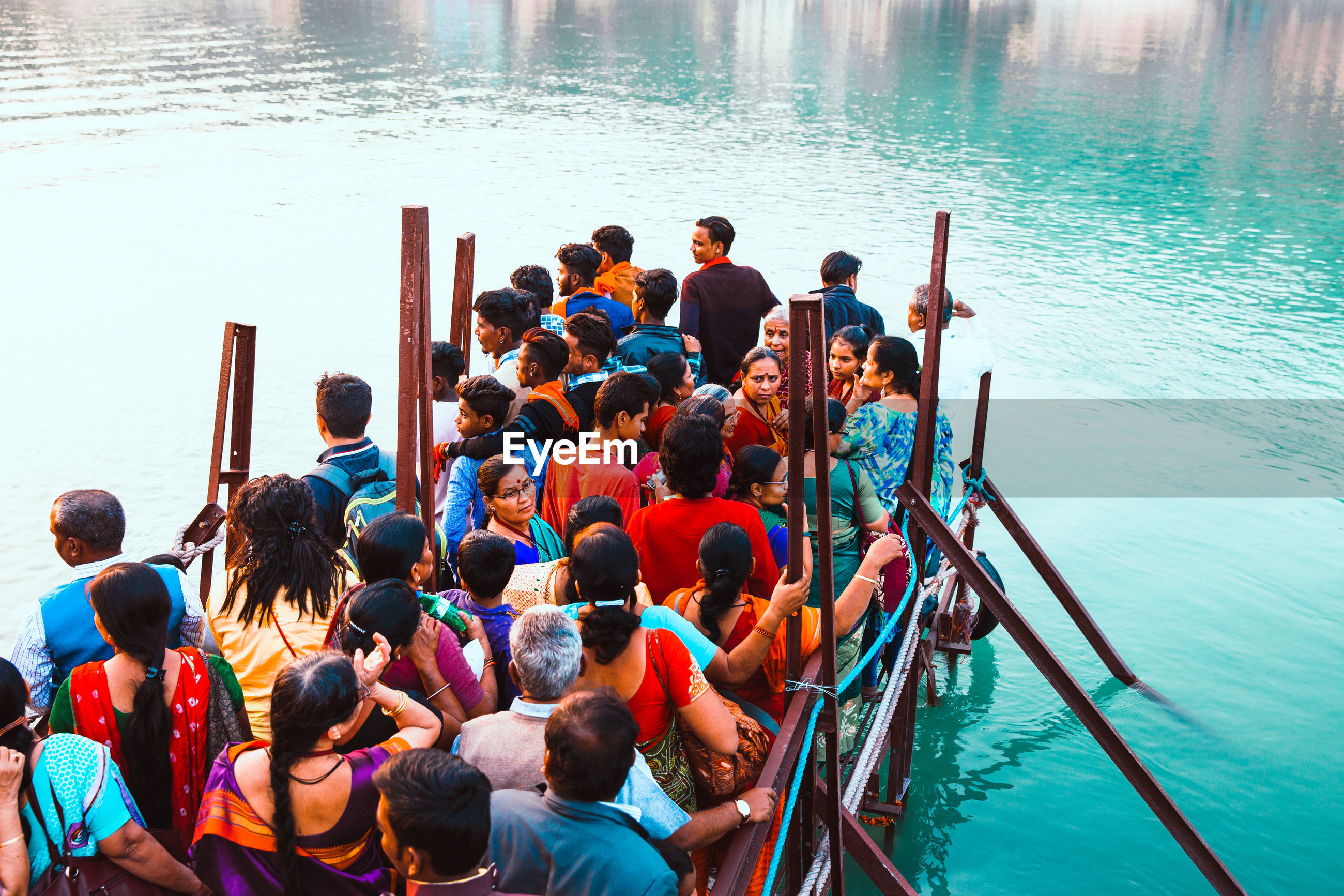 HIGH ANGLE VIEW OF PEOPLE SITTING AT LAKE