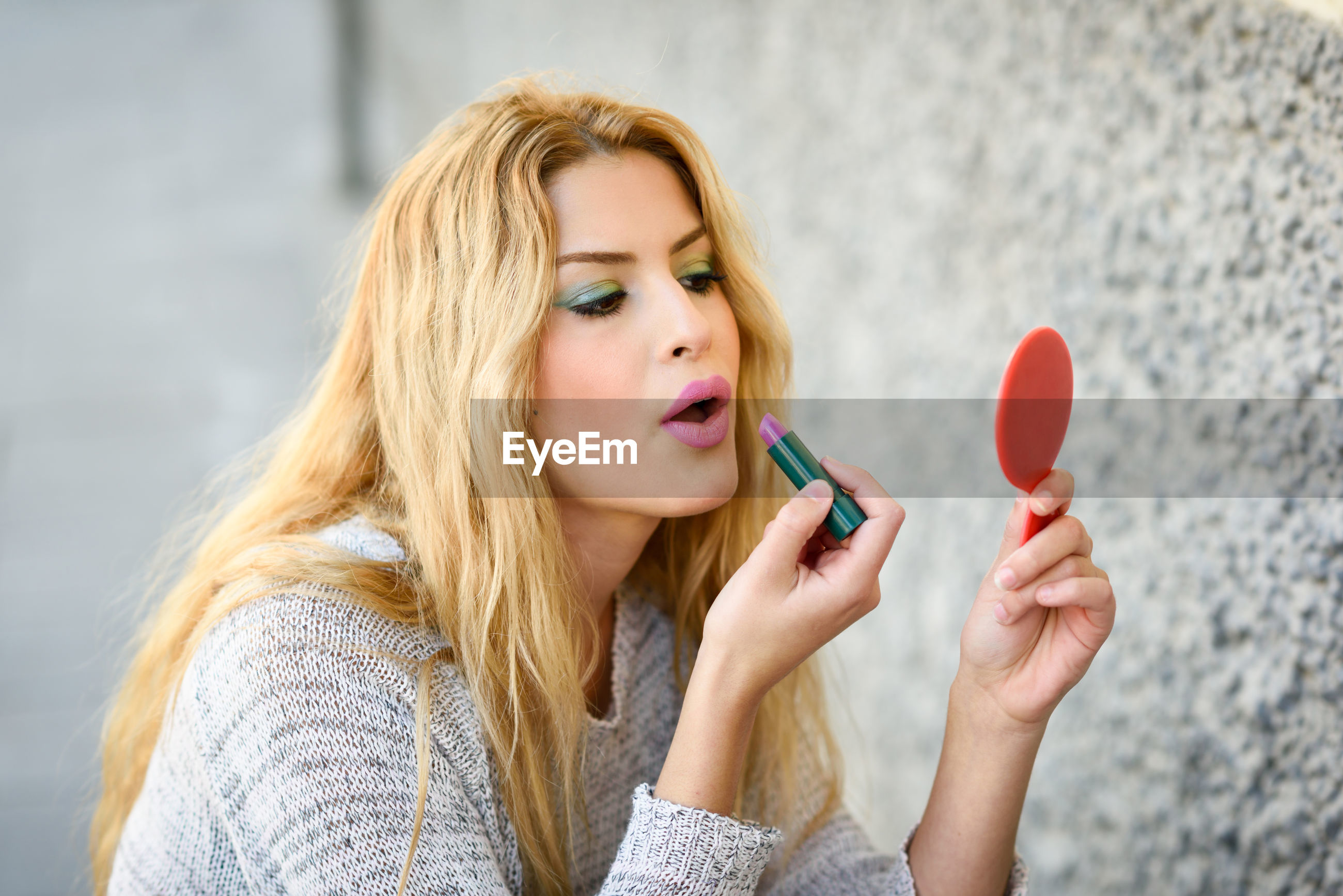 Close-up of young woman applying lipstick by wall