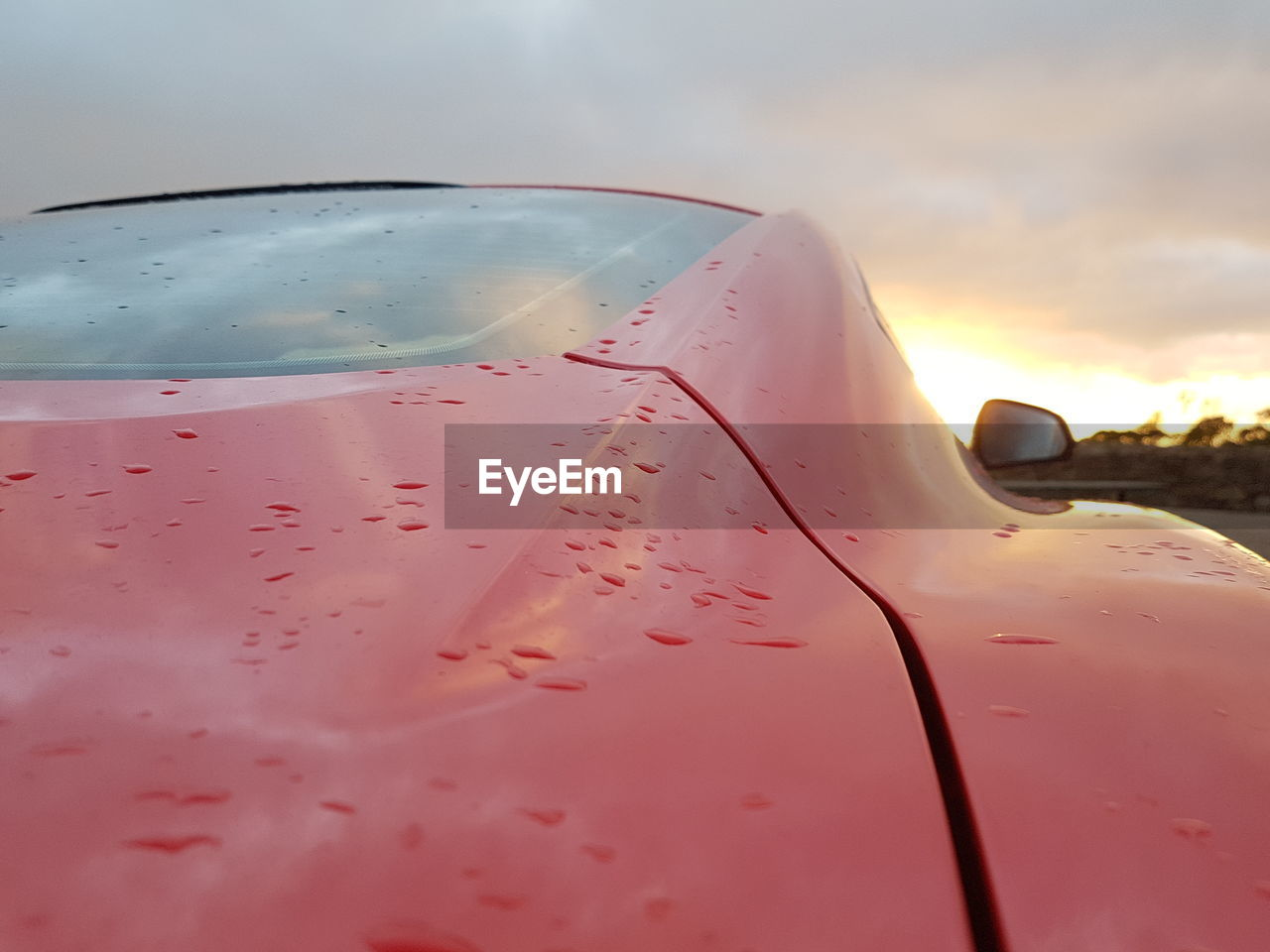 Close-up of wet car against sky during sunset