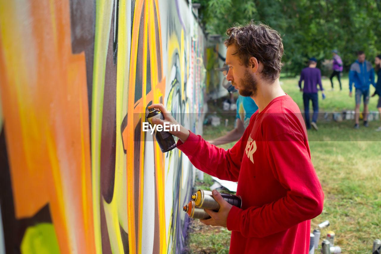 View Of Man Graffitiing Wall