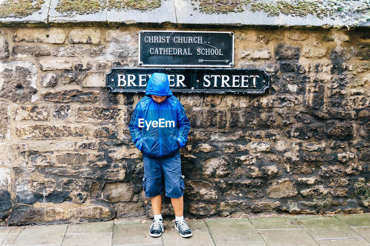 Full Length Of Boy In Hooded Jacket Standing Against Information Sign On Stone Wall
