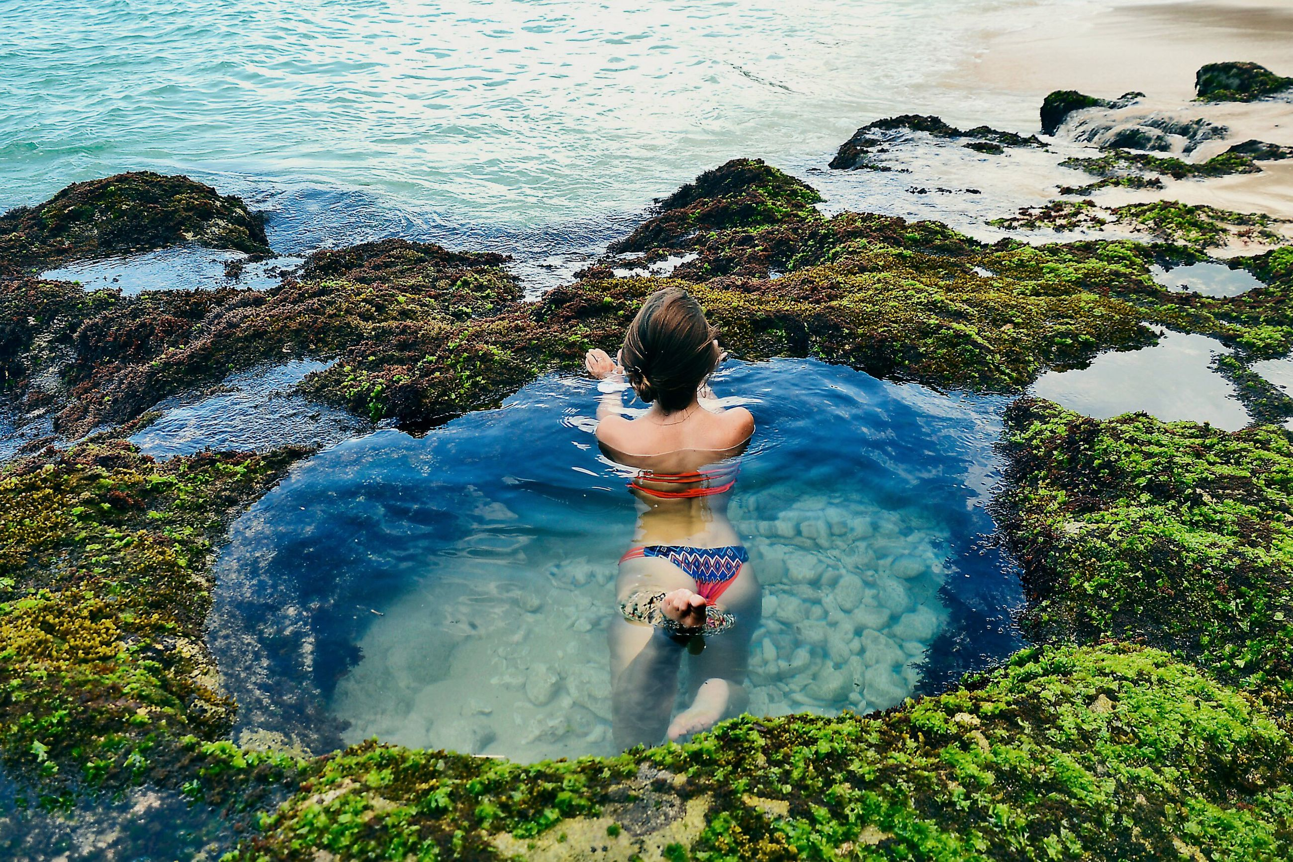 High angle view of woman in tidal pool at beach