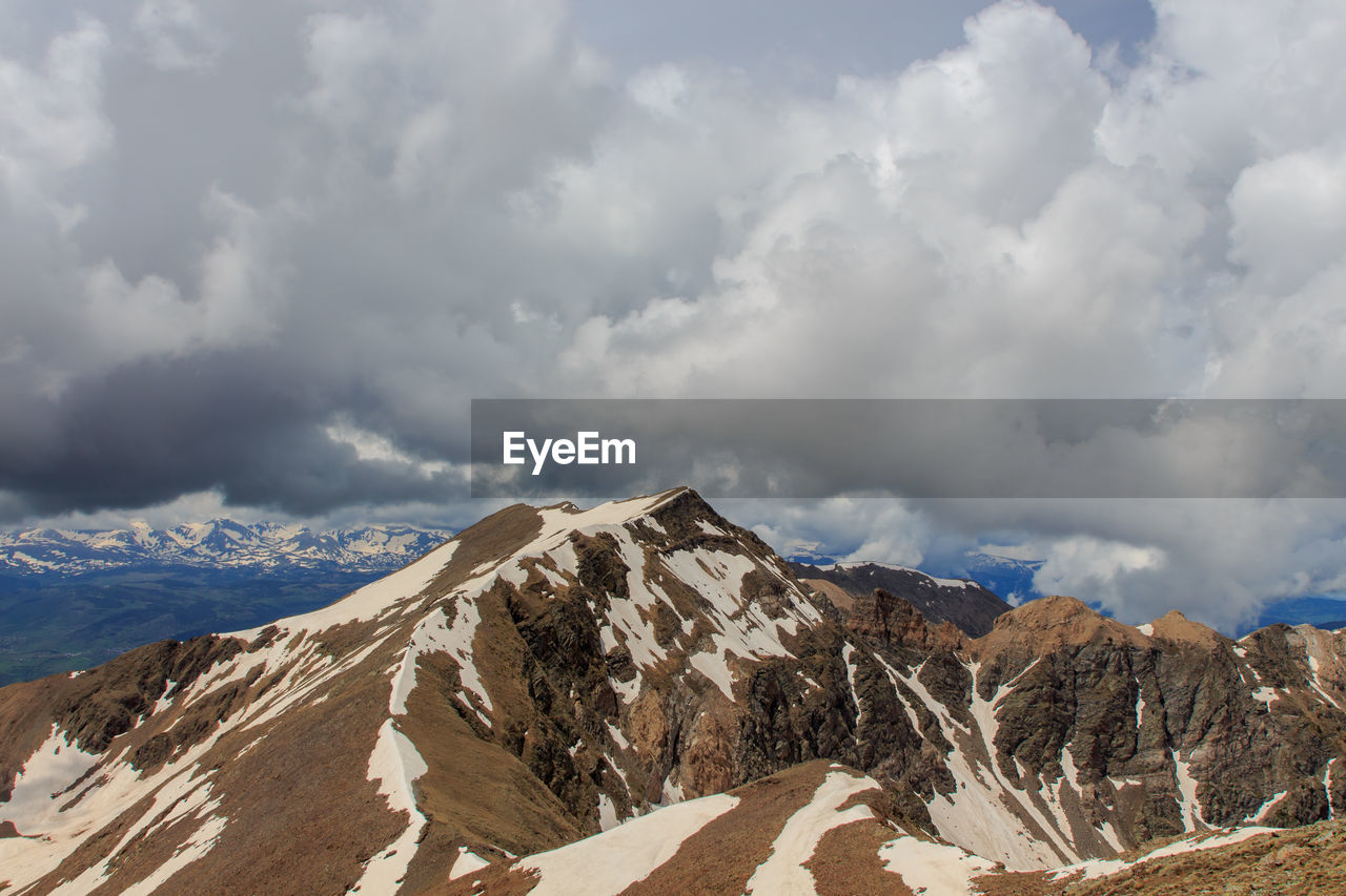 SCENIC VIEW OF SNOWCAPPED MOUNTAINS AGAINST CLOUDY SKY