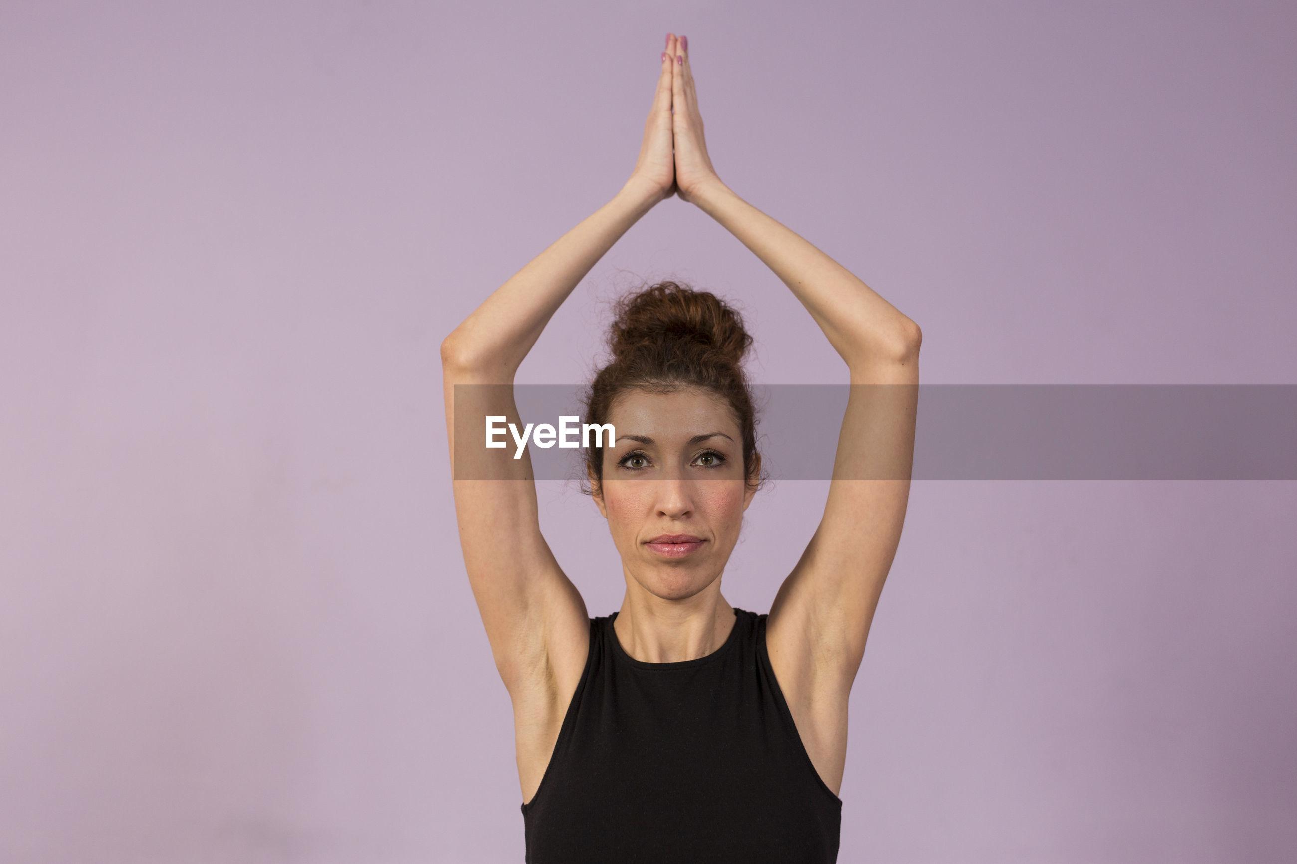 Portrait of woman doing yoga on purple background