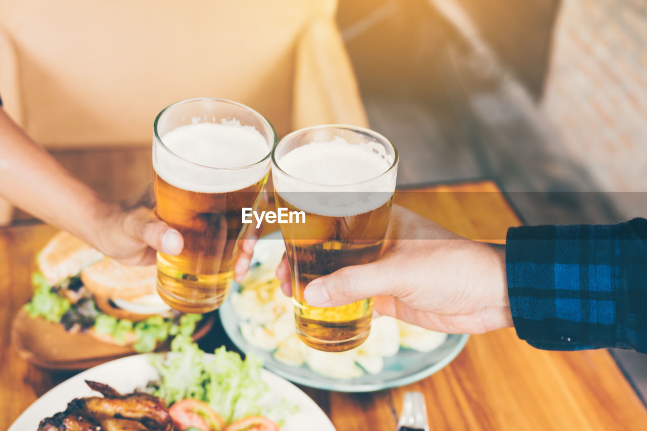 food and drink, human hand, alcohol, hand, drink, beer, refreshment, beer - alcohol, human body part, real people, table, freshness, holding, indoors, lifestyles, beer glass, men, adult, leisure activity, business, celebratory toast, glass, finger