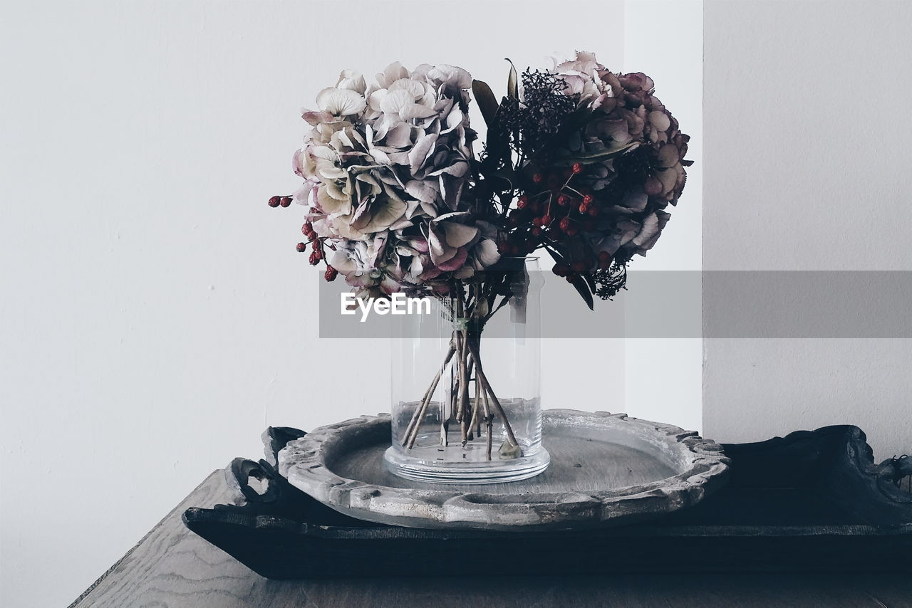 Close-Up Of Flower Vase In Tray On Table Against Wall