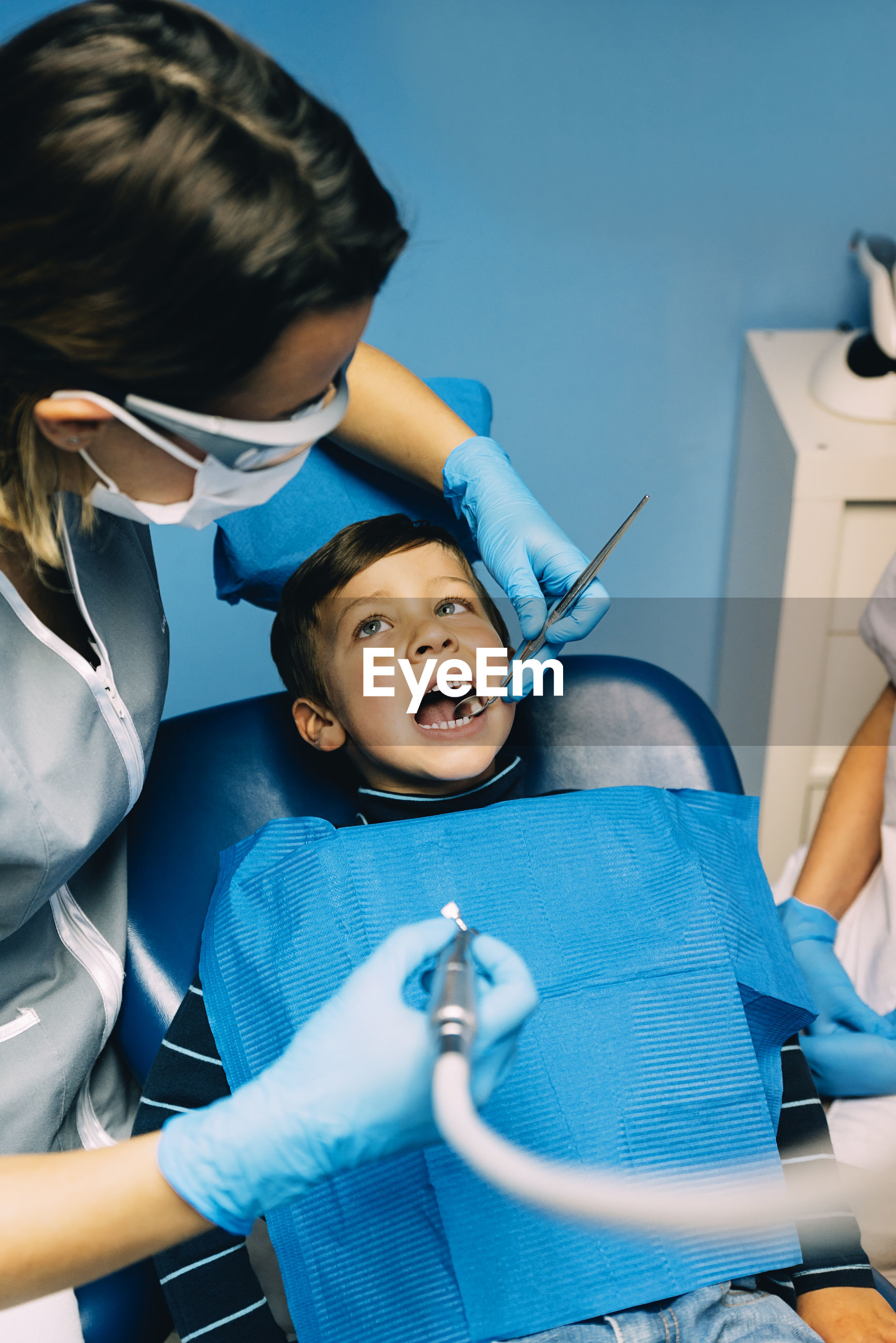 Dentists examining boy in clinic