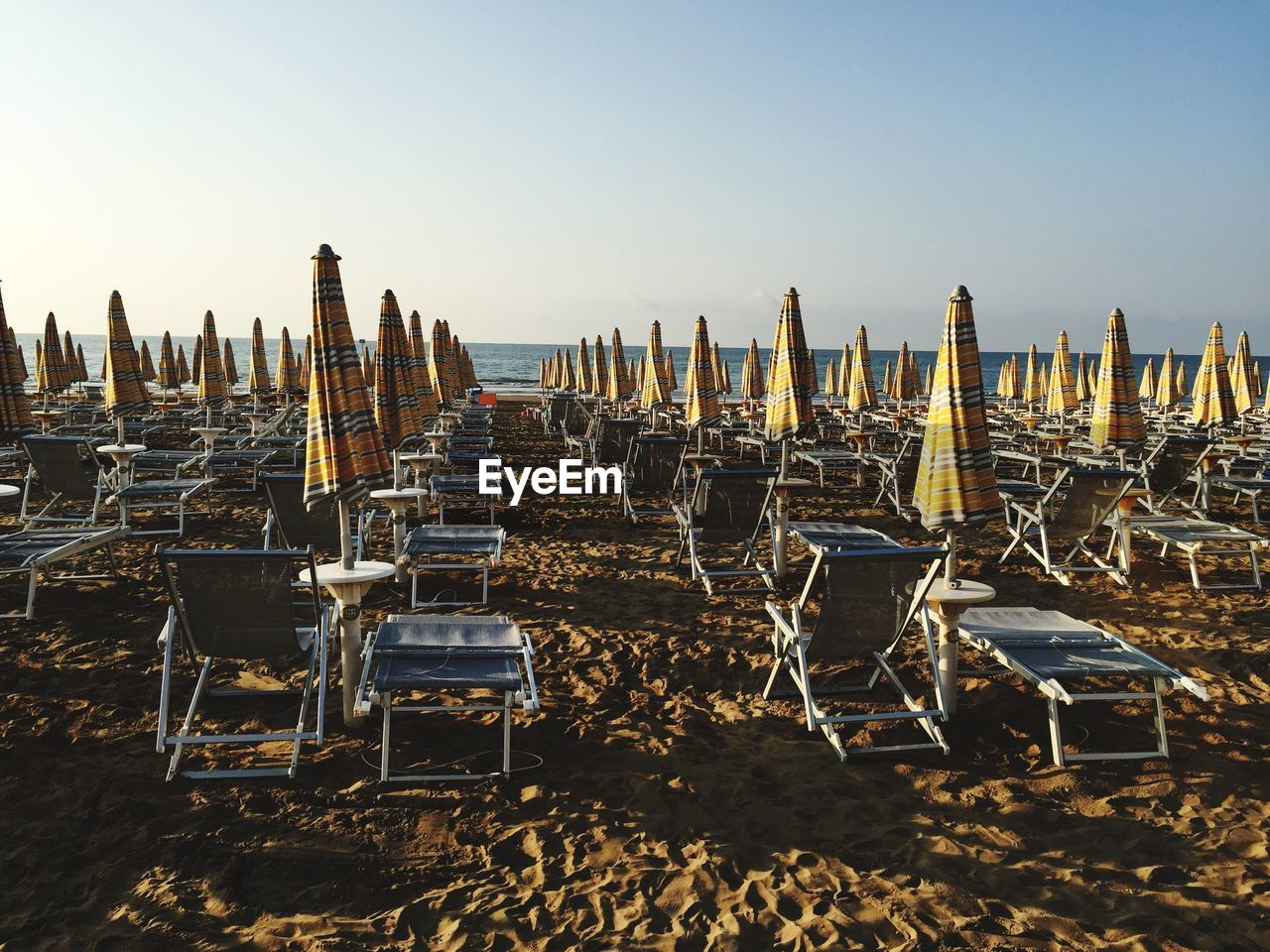 sky, chair, in a row, clear sky, nature, large group of objects, beach, seat, land, no people, lounge chair, absence, sea, tranquility, arrangement, water, parasol, day, sand, outdoors, order