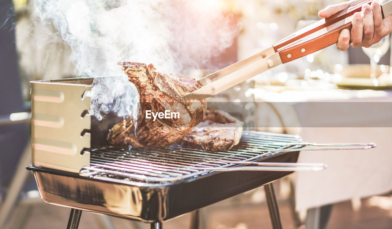 meat, food, food and drink, freshness, preparation, barbecue, smoke - physical structure, human hand, preparing food, heat - temperature, one person, hand, barbecue grill, real people, human body part, serving tongs, focus on foreground, unrecognizable person, grilled, finger