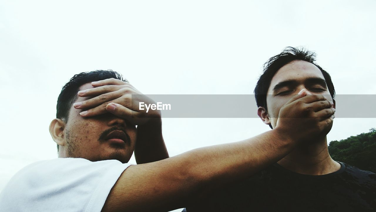 Low Angle View Of Friends Covering Eyes And Mouth Against Clear Sky