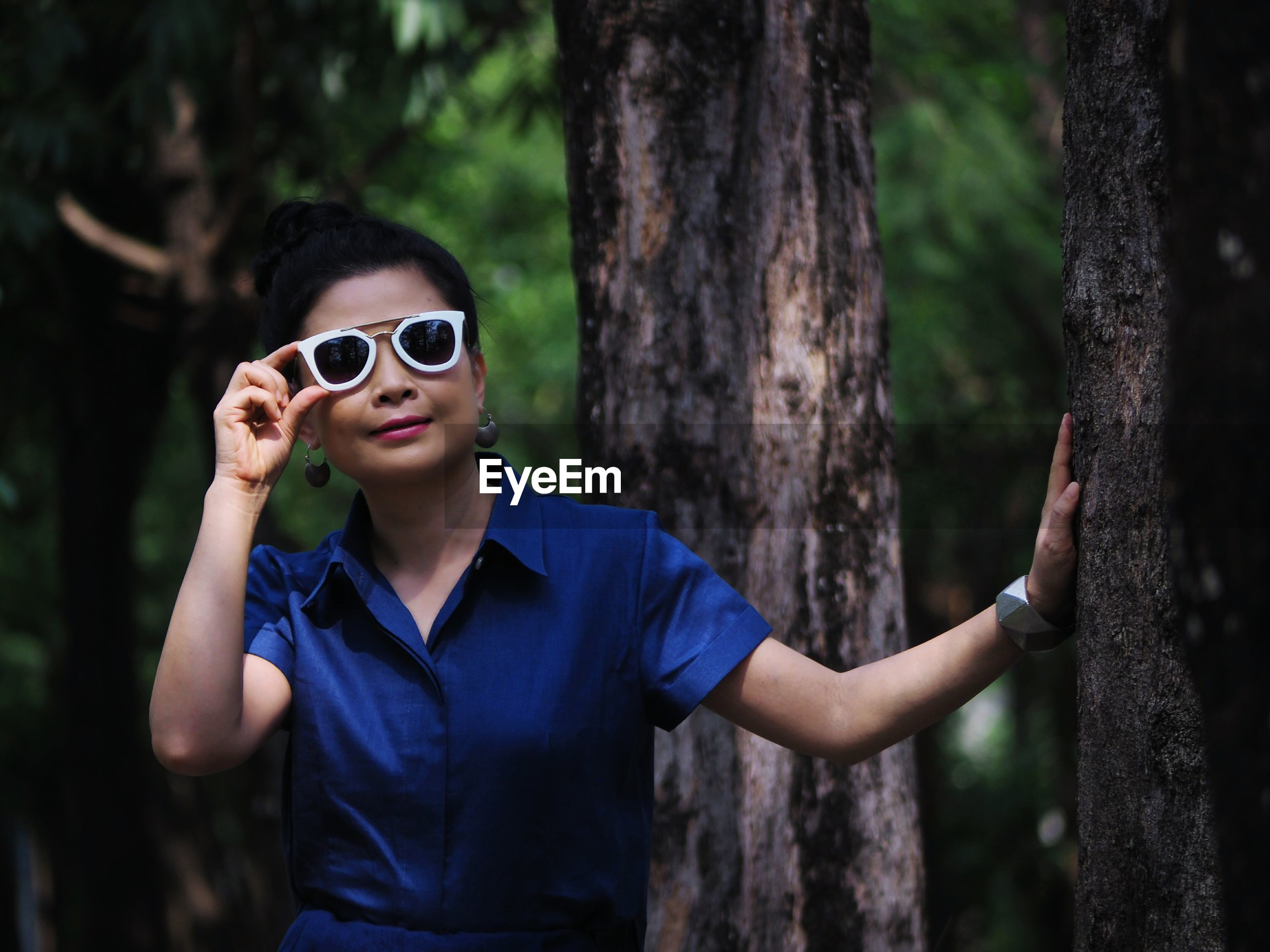 Portrait of woman in sunglasses standing by tree trunk