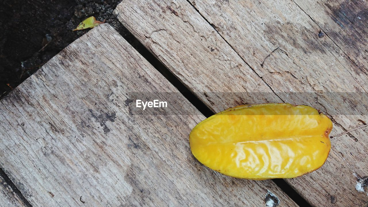 wood - material, yellow, food and drink, food, still life, high angle view, no people, close-up, freshness, table, healthy eating, day, wellbeing, fruit, outdoors, directly above, nature, textured, sweet food, slice, temptation