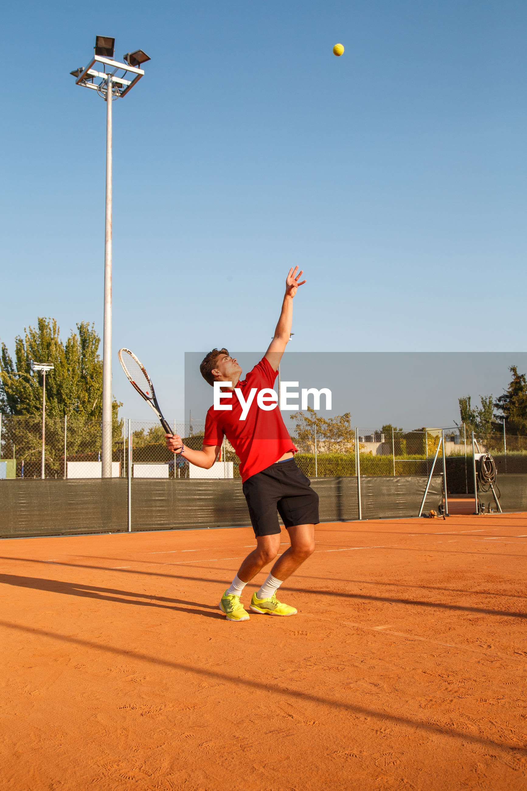 Man playing tennis on court against clear blue sky