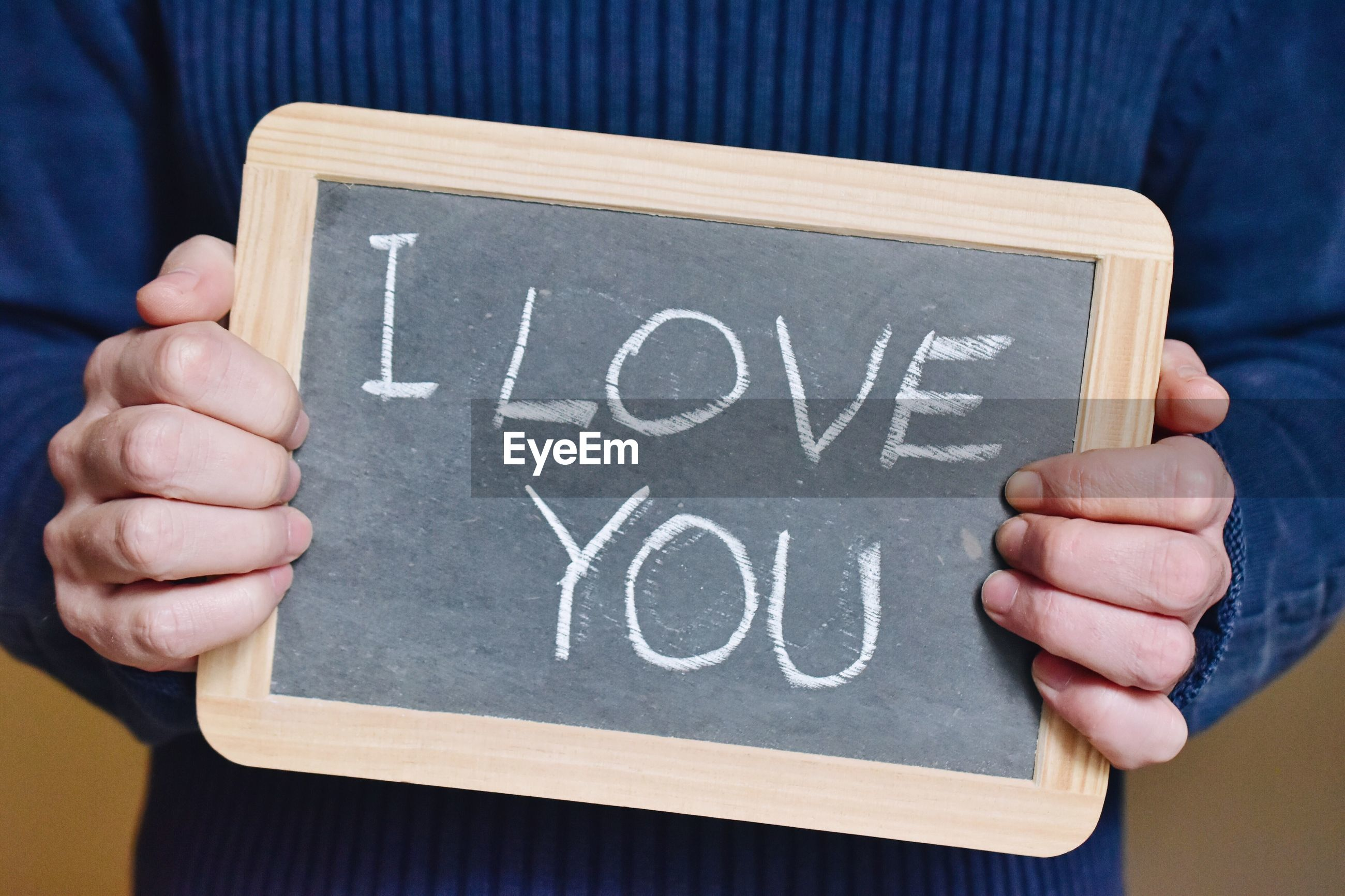 Midsection of person holding slate with i love you message