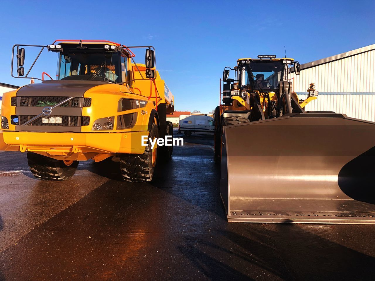 land vehicle, transportation, mode of transportation, machinery, industry, construction industry, sky, construction machinery, road, yellow, commercial land vehicle, construction site, development, clear sky, outdoors, nature, motor vehicle, sunlight, bulldozer, equipment, construction equipment, industrial equipment