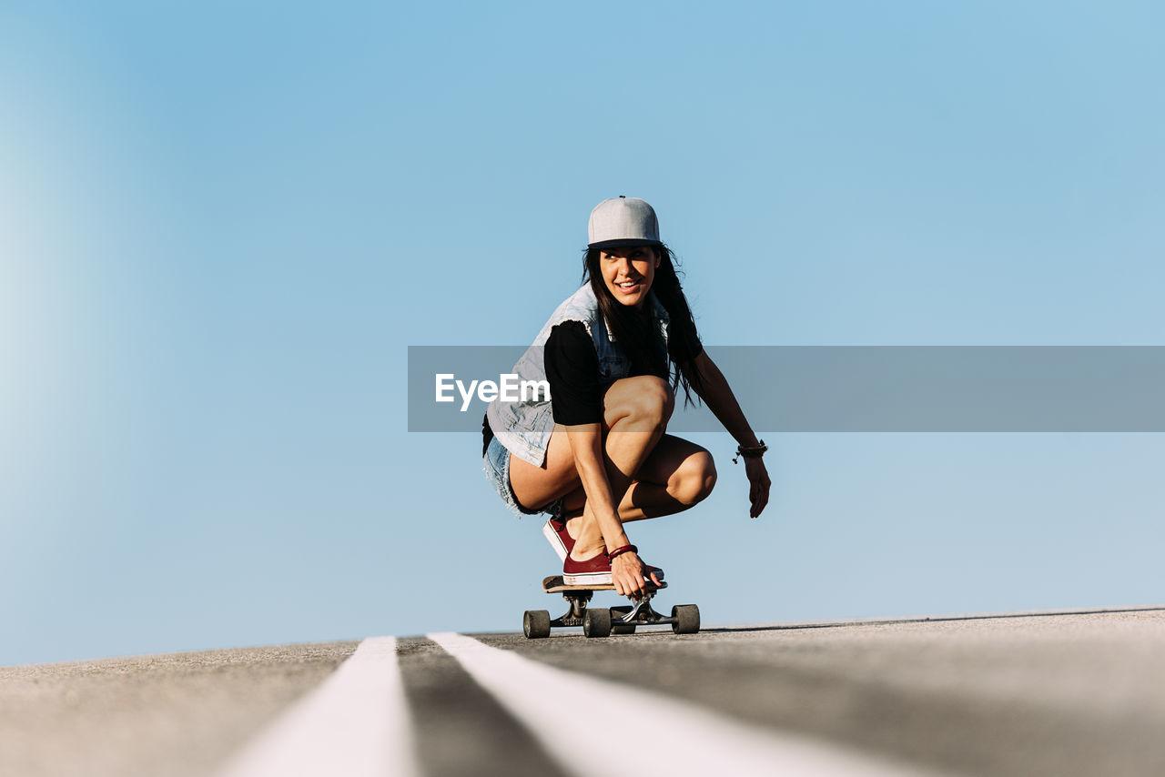 Woman skateboarding against blue sky