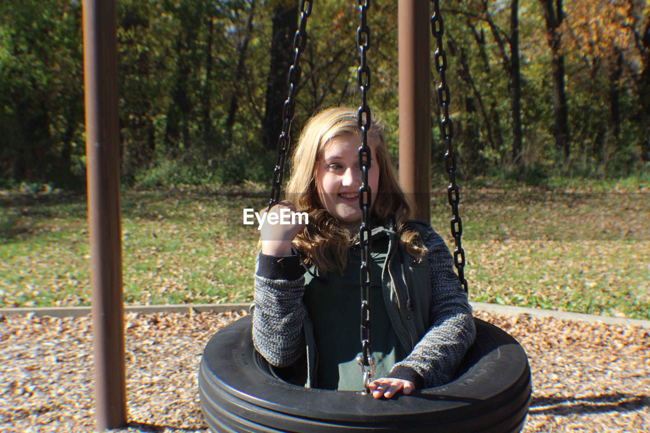 Teenage girl sitting on tire swing
