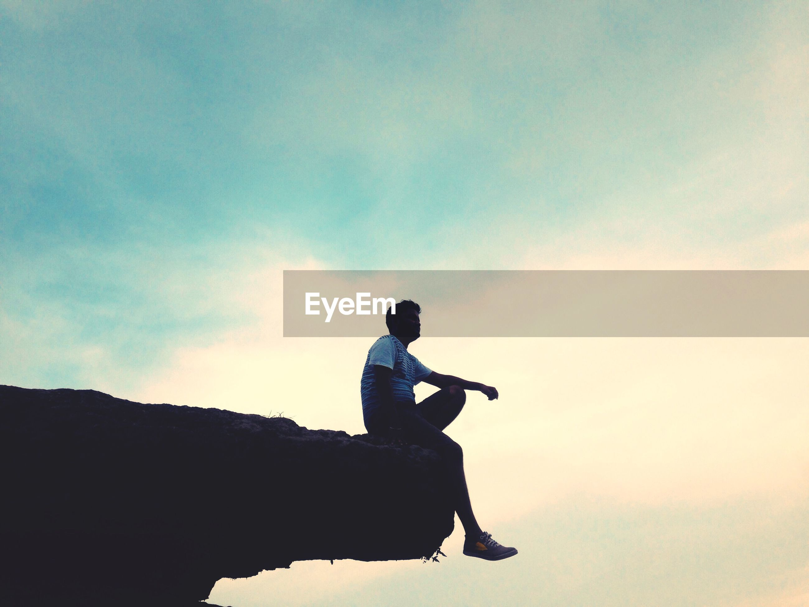 Low angle view of man sitting on cliff against sky