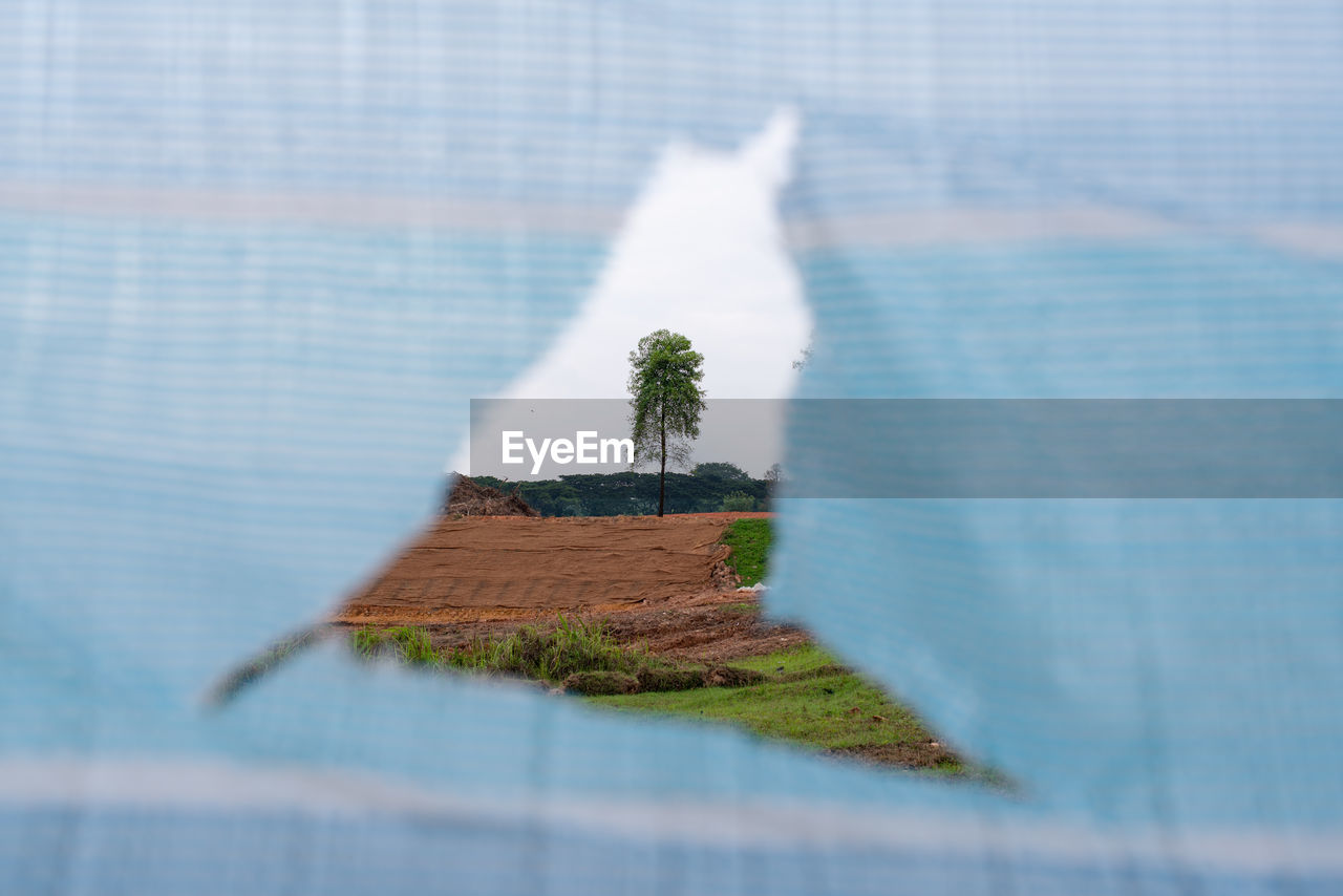architecture, plant, no people, selective focus, nature, day, built structure, outdoors, landscape, field, close-up, grass, building exterior, focus on background, blue, land, water, sunlight, wall - building feature, digital composite