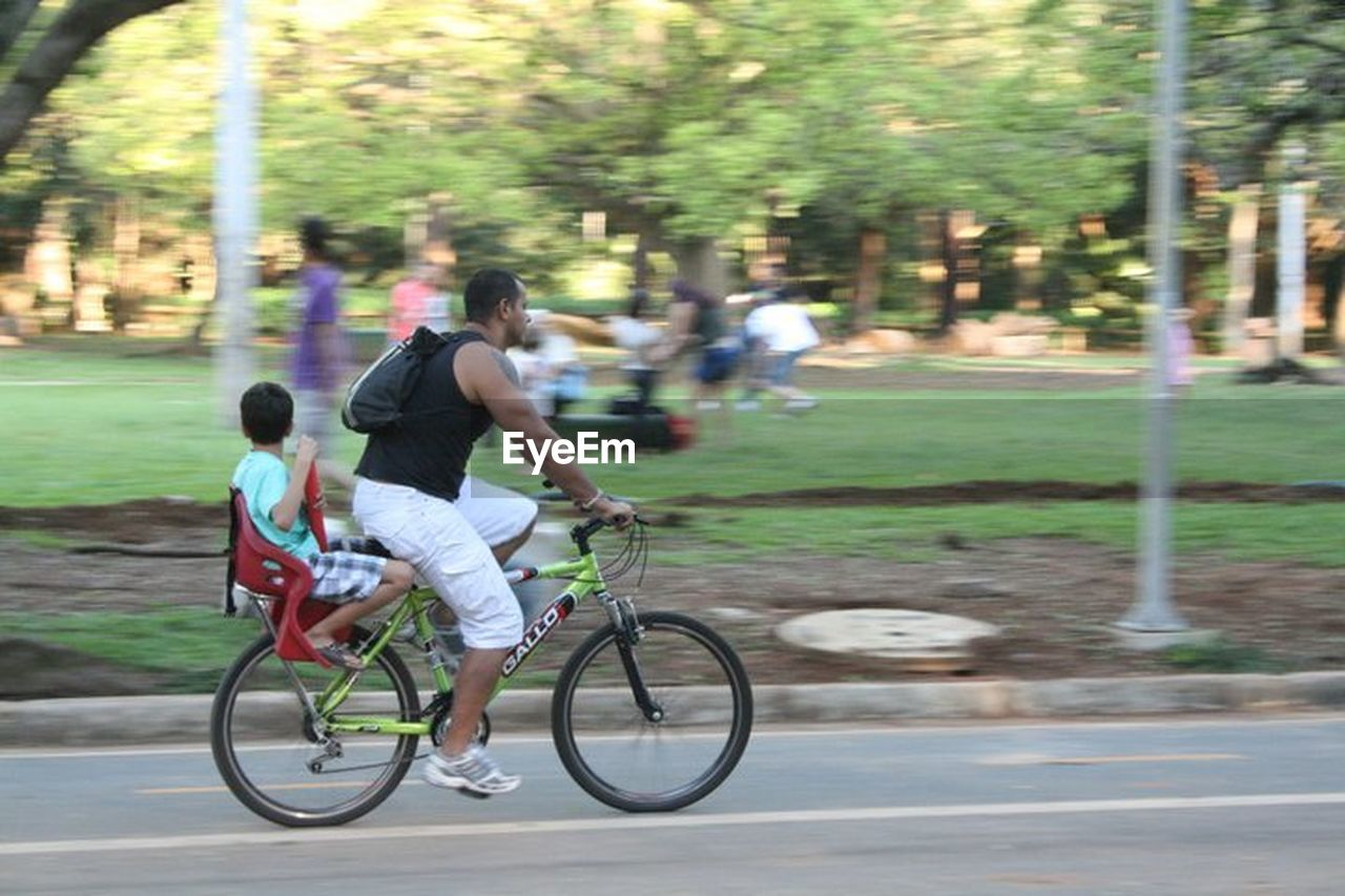 bicycle, cycling, riding, real people, motion, transportation, blurred motion, leisure activity, men, lifestyles, togetherness, full length, day, women, two people, healthy lifestyle, exercising, outdoors, mountain bike, nature, city, adult, people