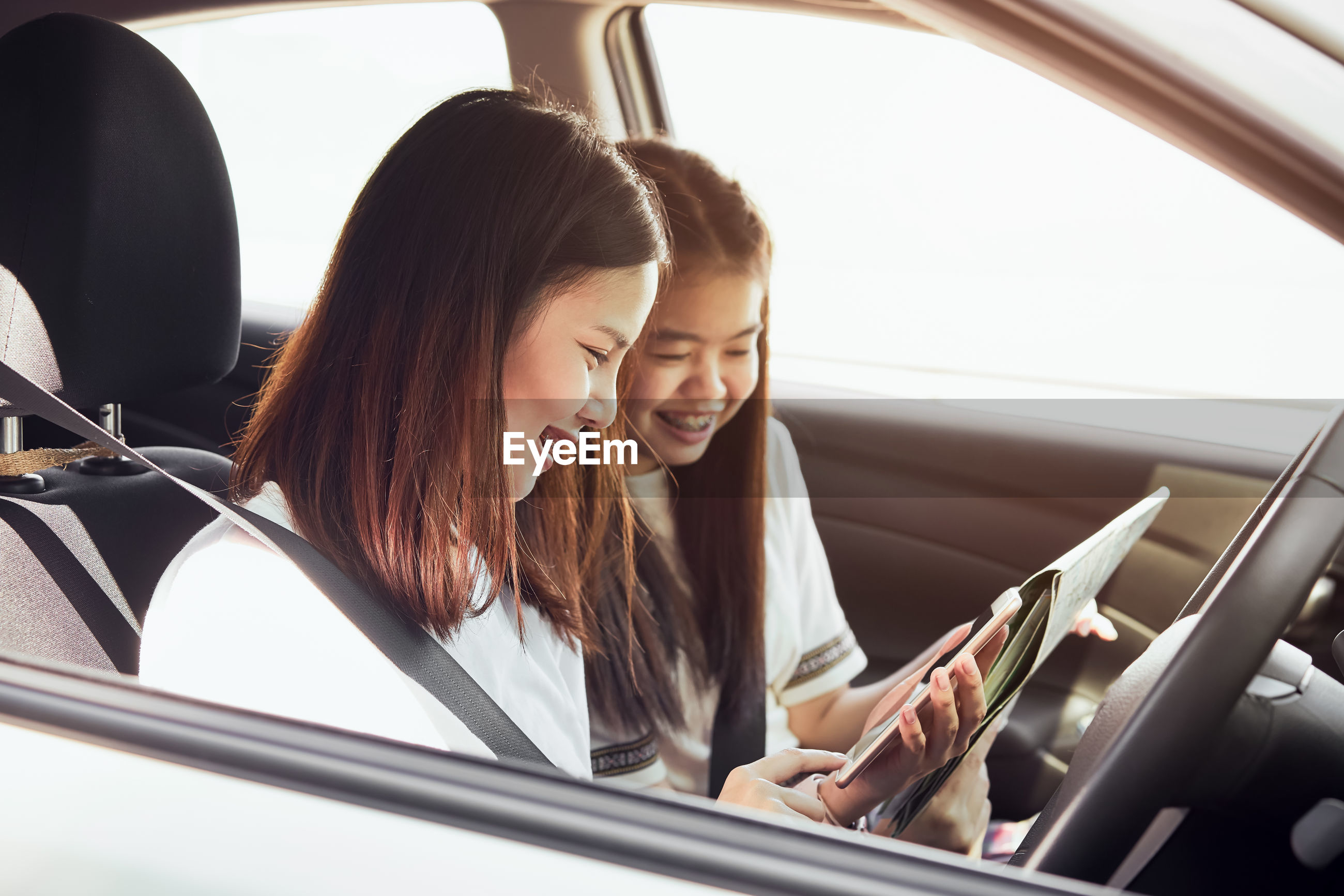 Smiling friends using phone while sitting in car
