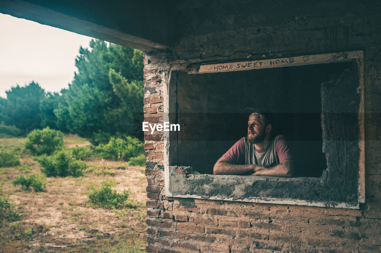 Man Looking Through Window Of Incomplete House