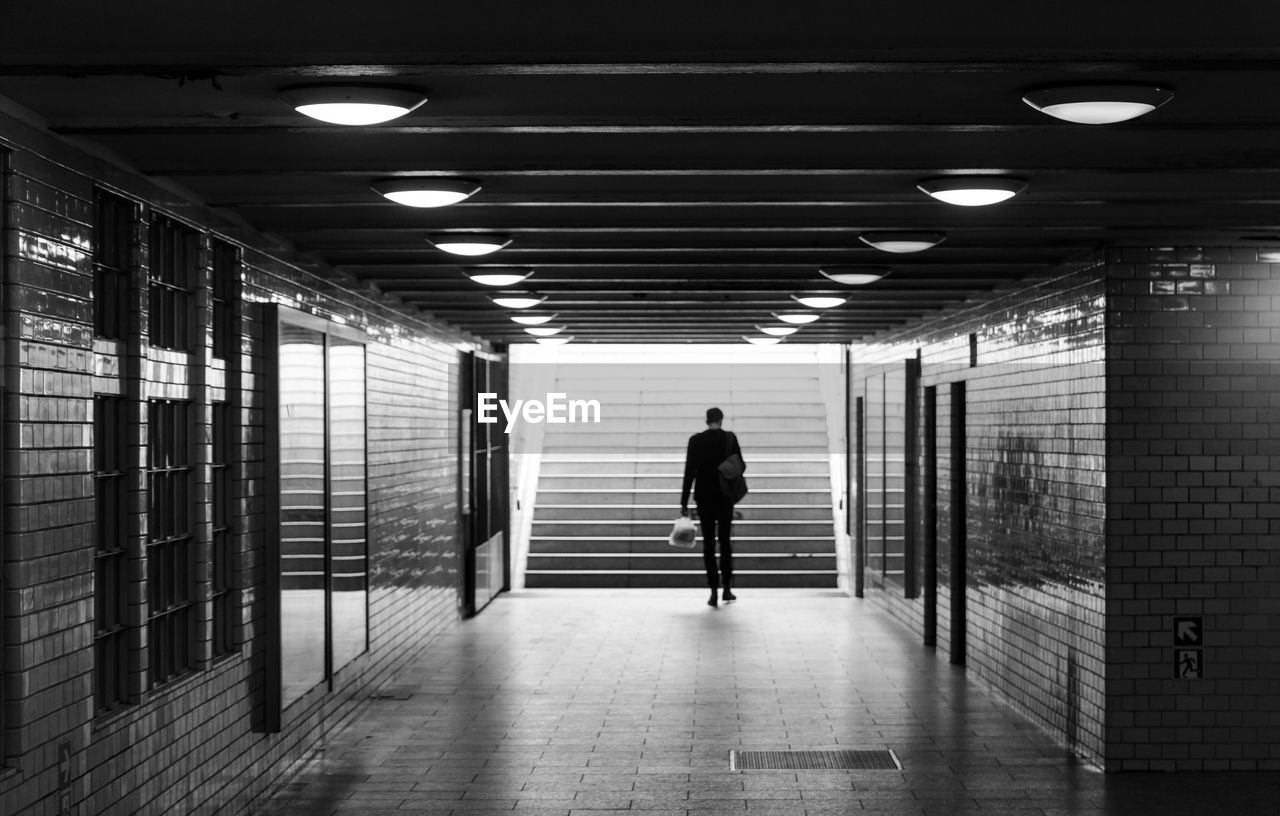 Rear View Of Man Walking Towards Staircase At Underground Walkway