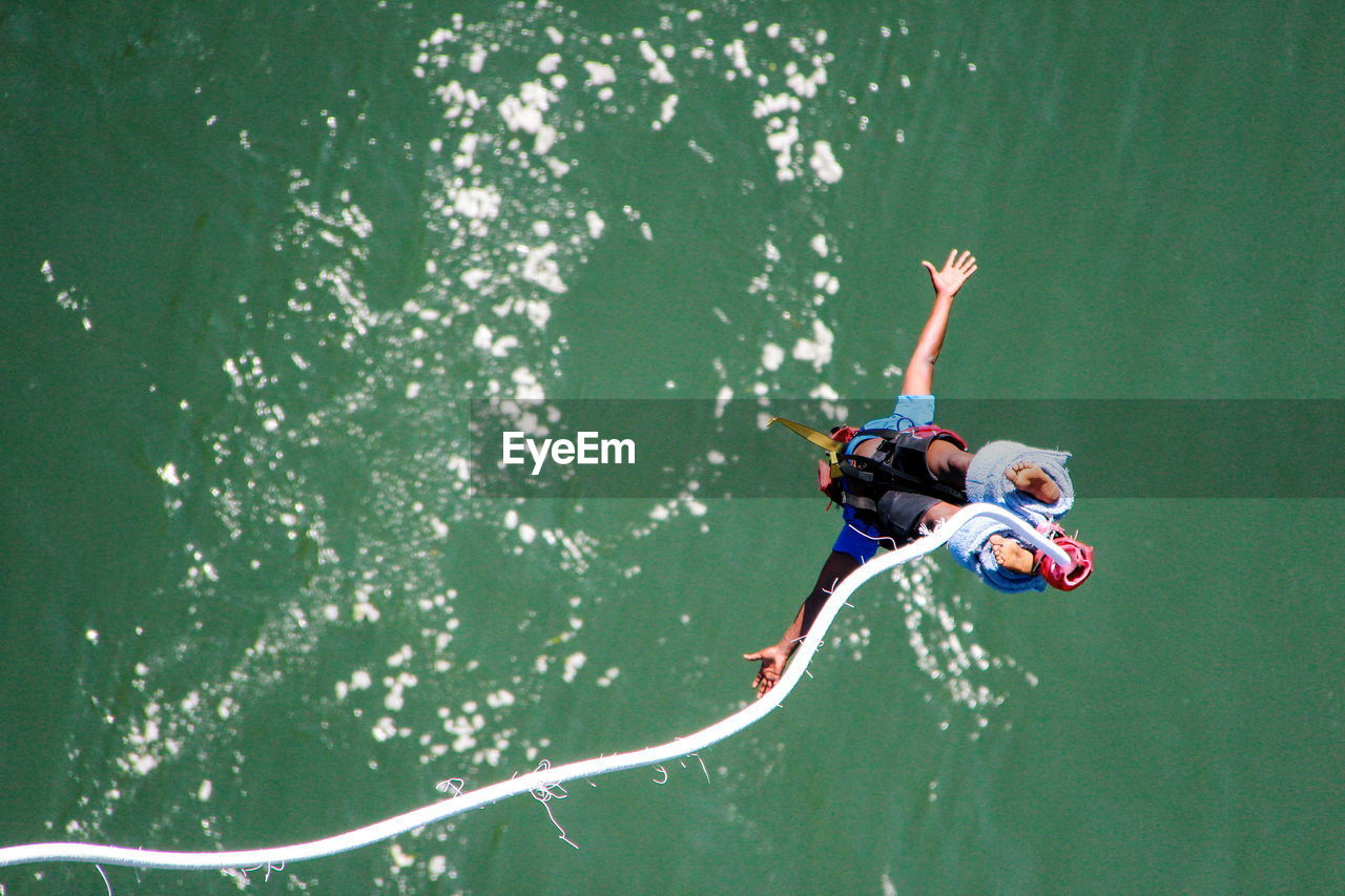 High angle view of man bungee jumping in river