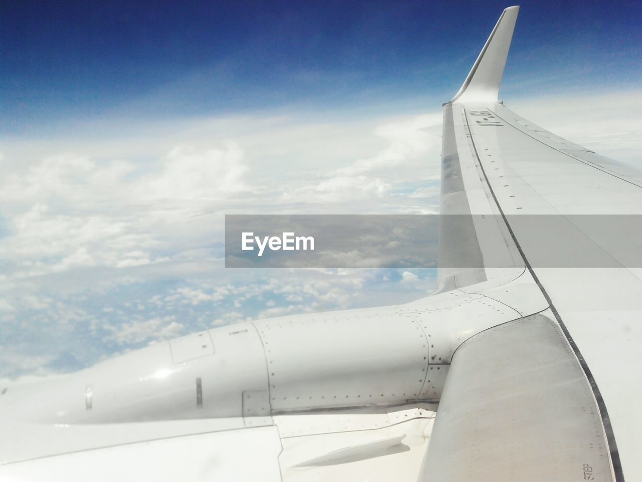 CROPPED IMAGE OF AIRPLANE WING OVER CLOUDS