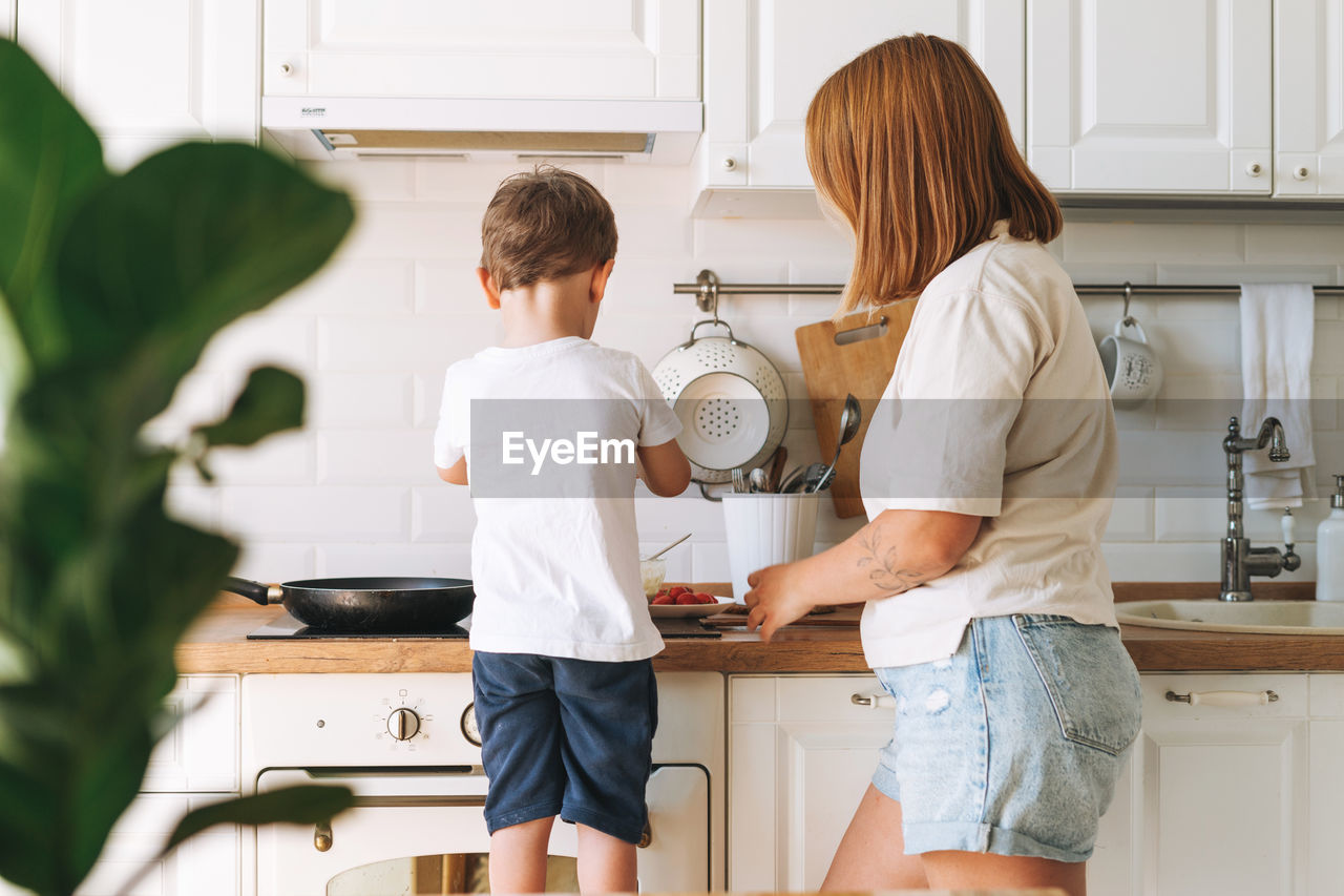 Cute toddler boy with mother cooking breakfast with puncakes together in bright kitchen at home