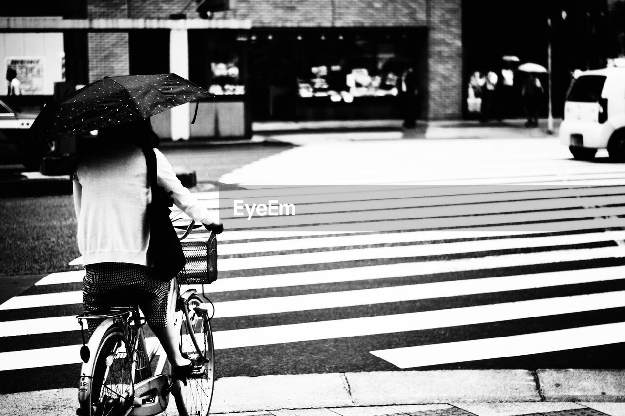 Rear view of woman with bicycle walking on road