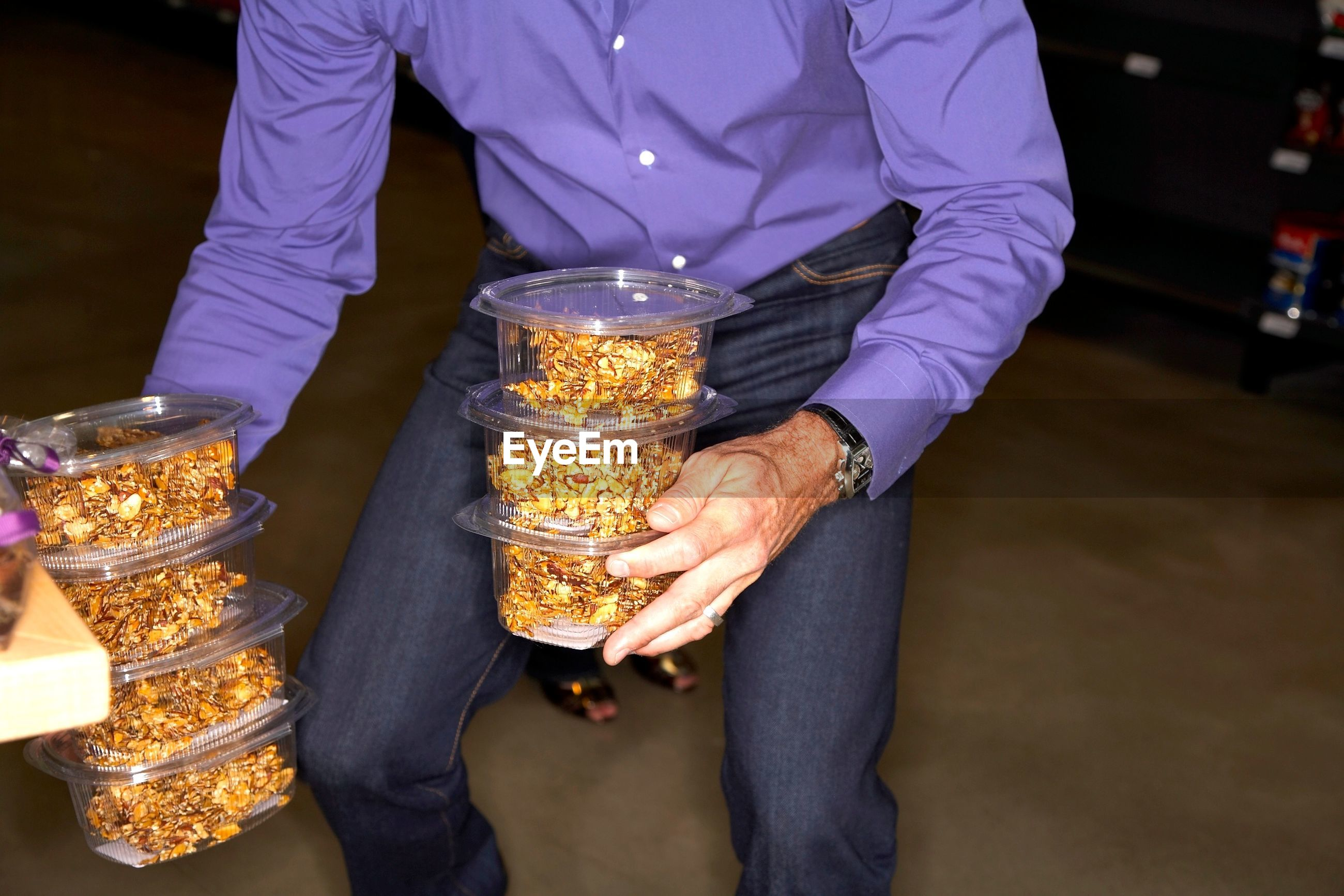 Midsection of man holding food baskets at night