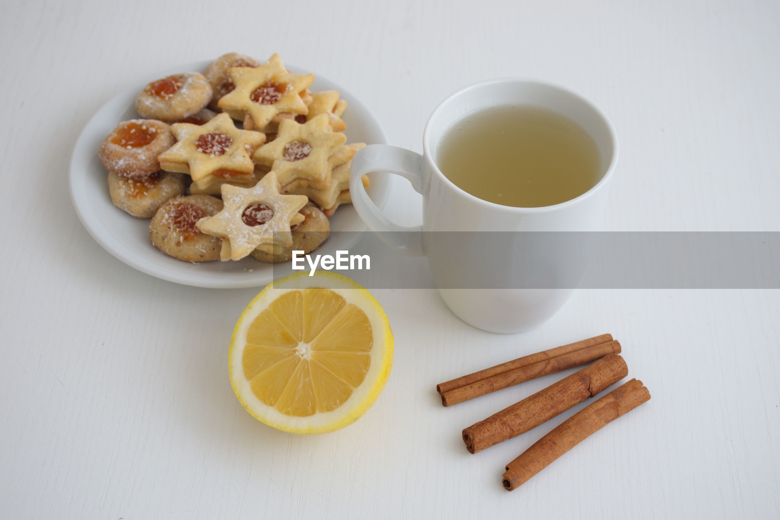 Cup of tea, lemon, cinnamon and plate with cookies against the white background