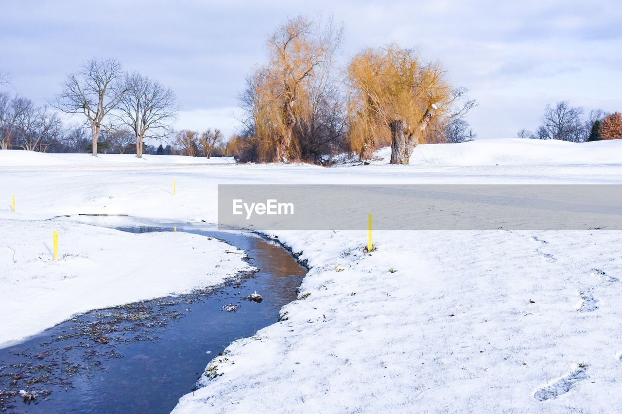 Stream Amidst Snow Covered Field Against Sky