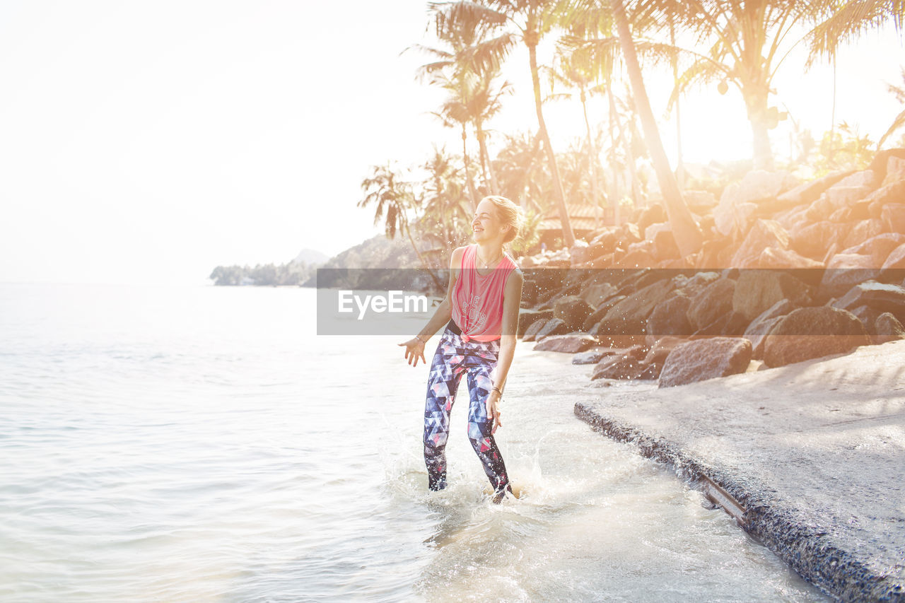 Happy Mid Adult Woman Standing At Beach During Sunny Day
