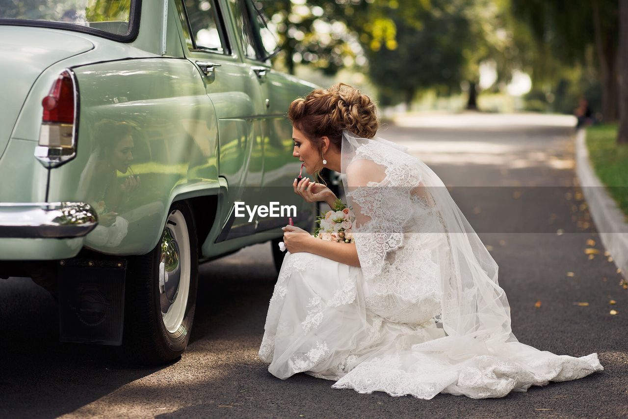 Side View Of Bride Applying Lipstick By Car