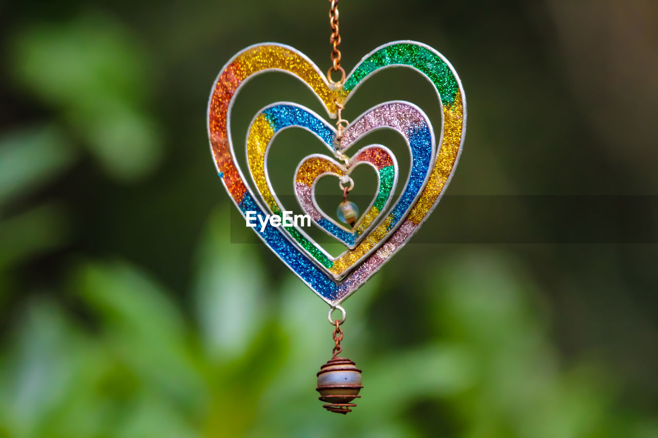 Close-up of heart shape pendants hanging outdoors