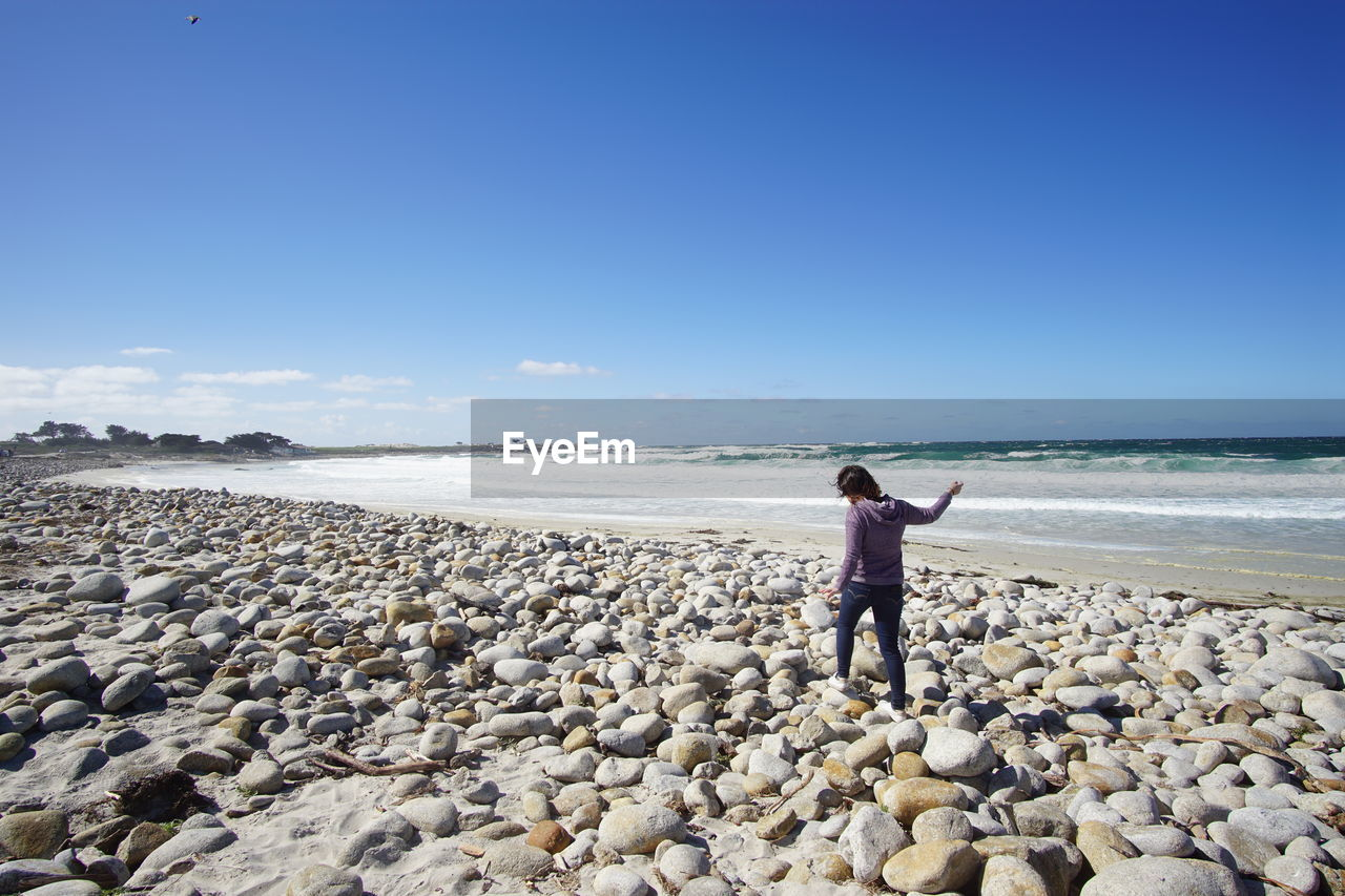 sky, sea, water, rock, solid, one person, beach, real people, beauty in nature, land, rock - object, standing, lifestyles, nature, scenics - nature, leisure activity, full length, rear view, horizon, horizon over water, pebble, outdoors