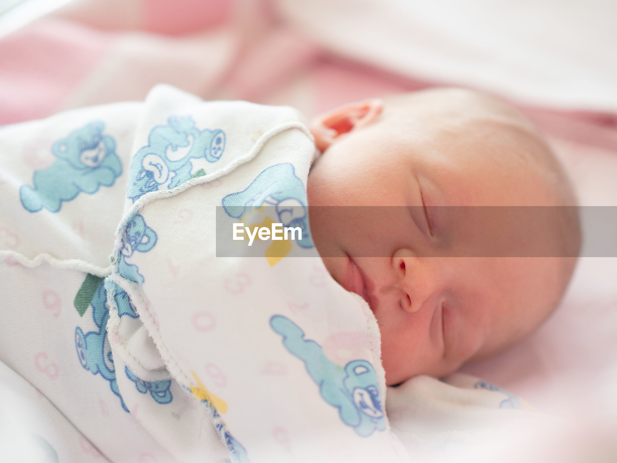 Close-up of baby sleeping in bed