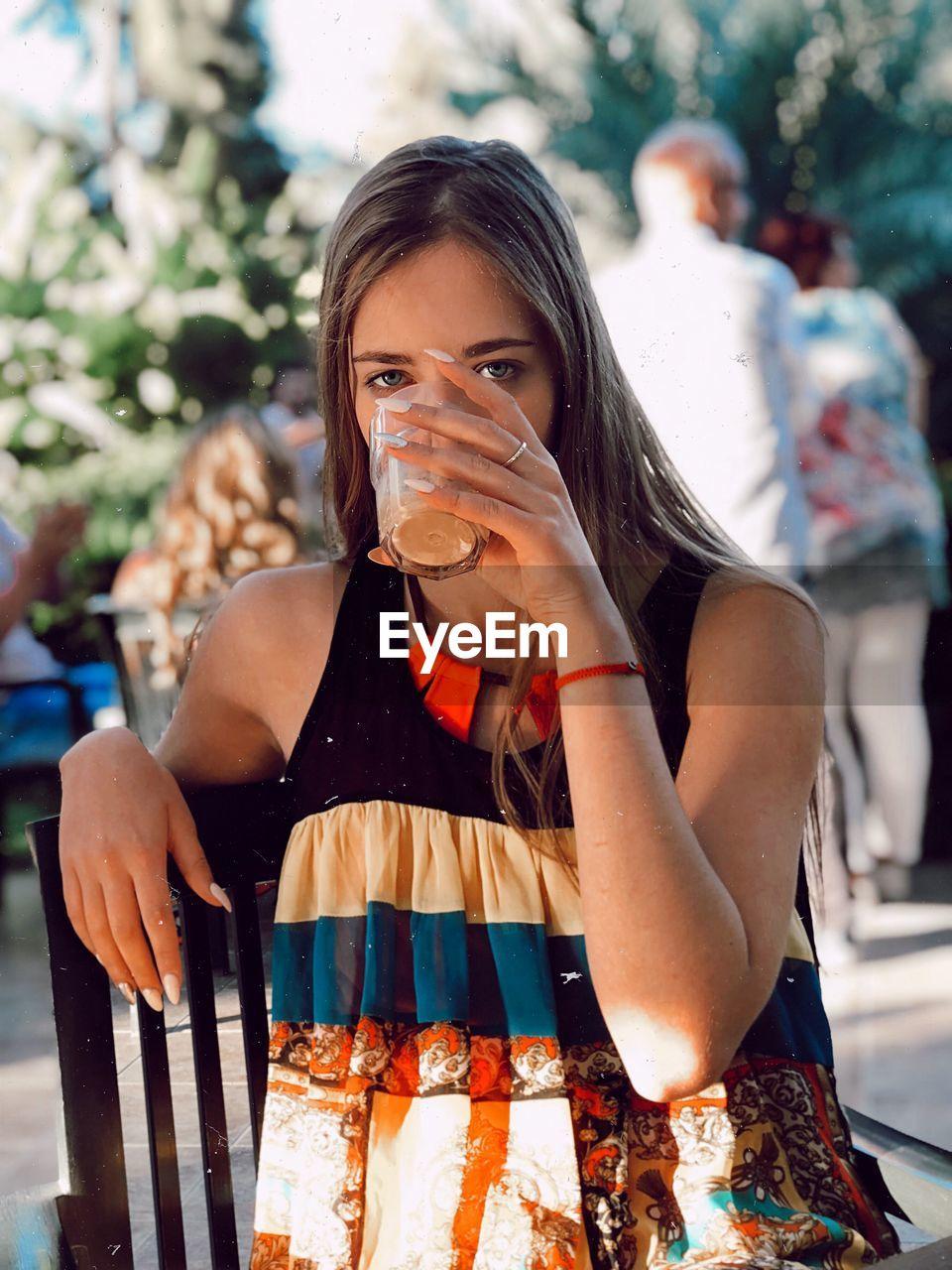 Portrait of woman drinking juice in glass
