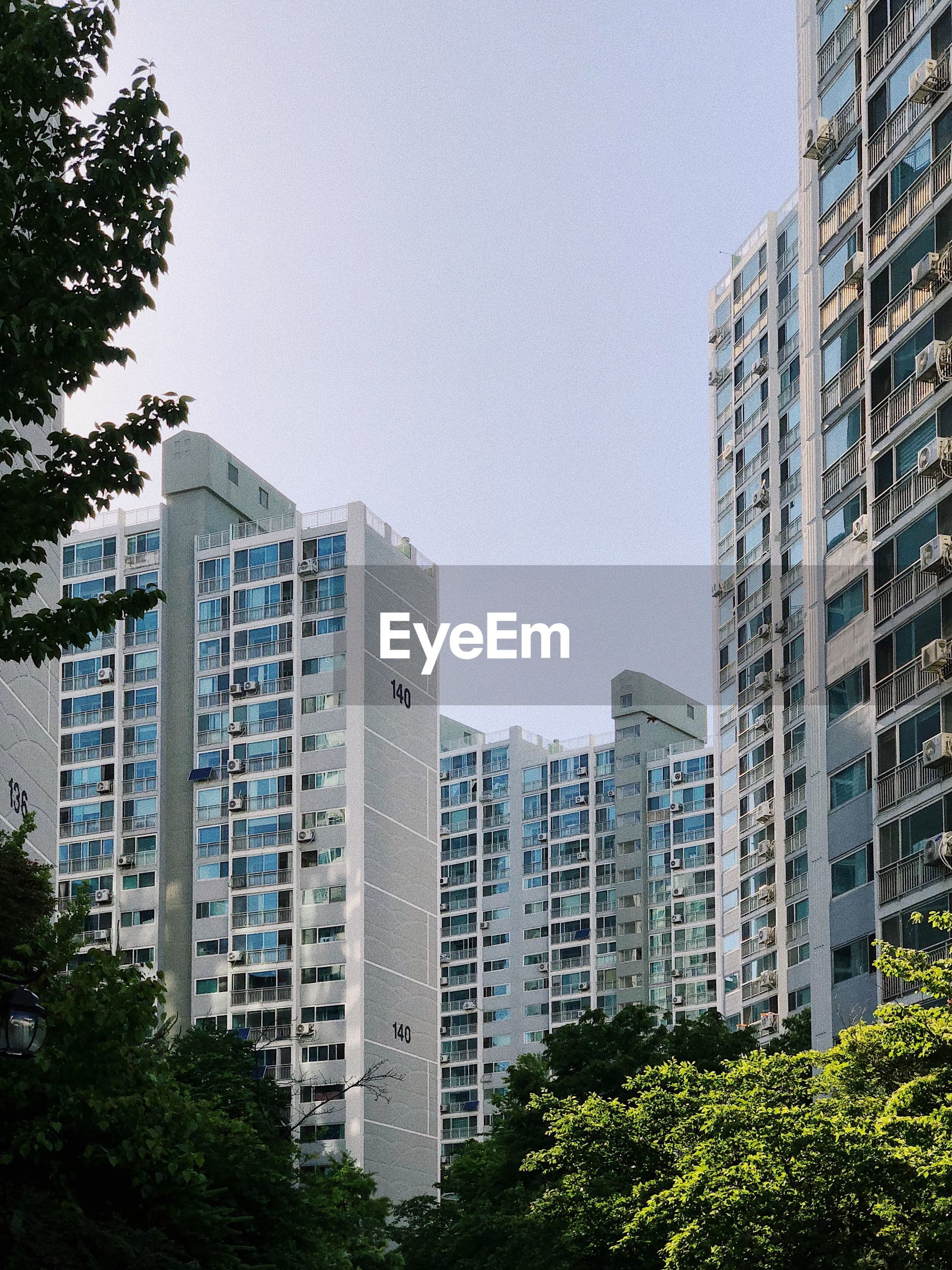 building exterior, architecture, built structure, tree, plant, sky, building, city, nature, no people, clear sky, day, low angle view, residential district, office building exterior, modern, office, outdoors, tall - high, tower, skyscraper, apartment