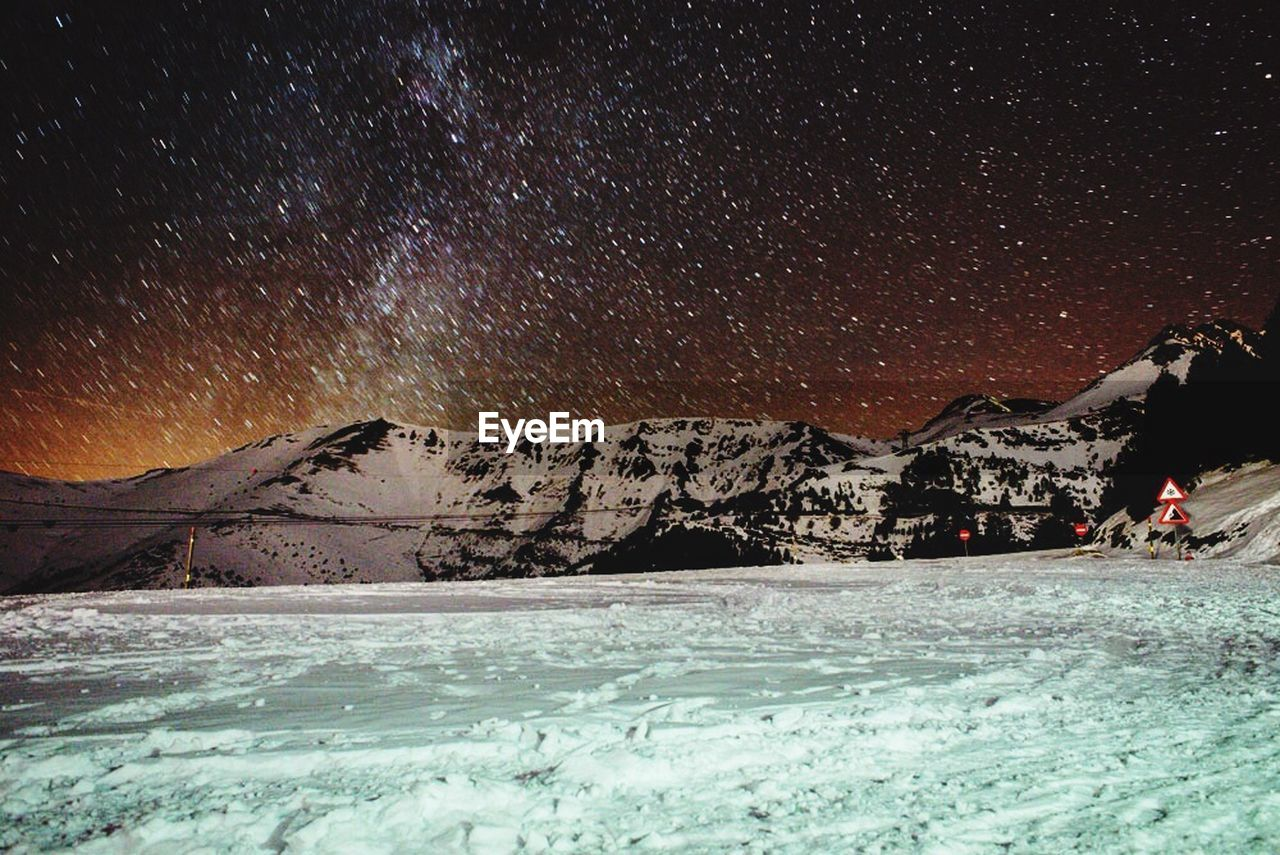 View of flakes with snow covered mountain and landscape at night