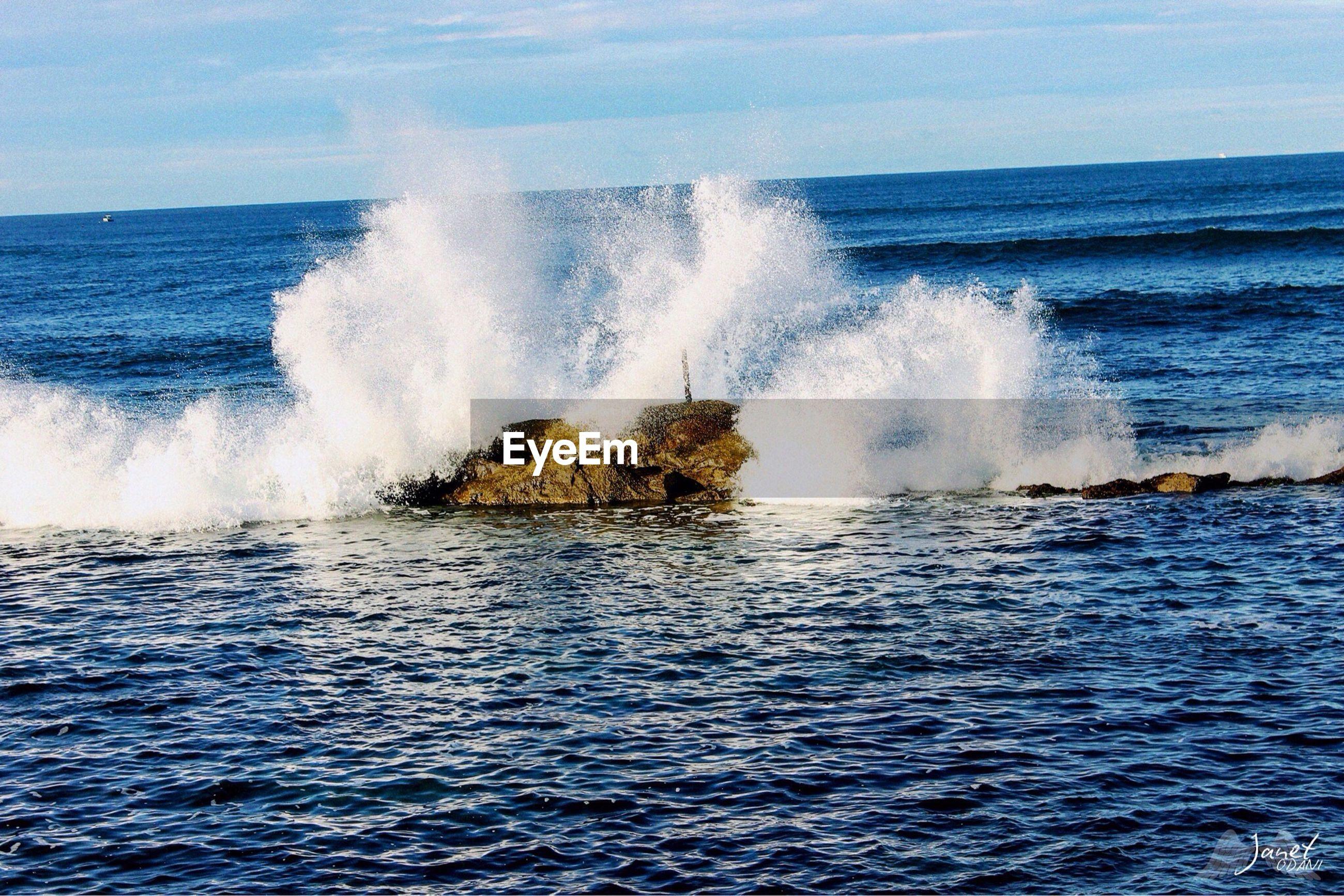 VIEW OF WAVES SPLASHING IN SEA AGAINST SKY