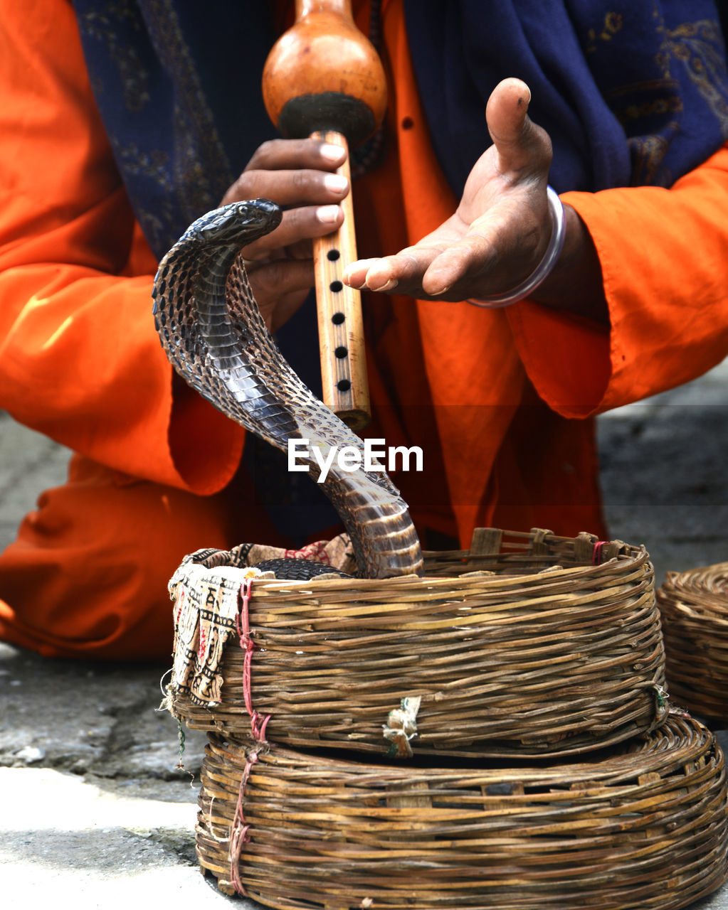 Low section of charmer playing flute by snake in basket
