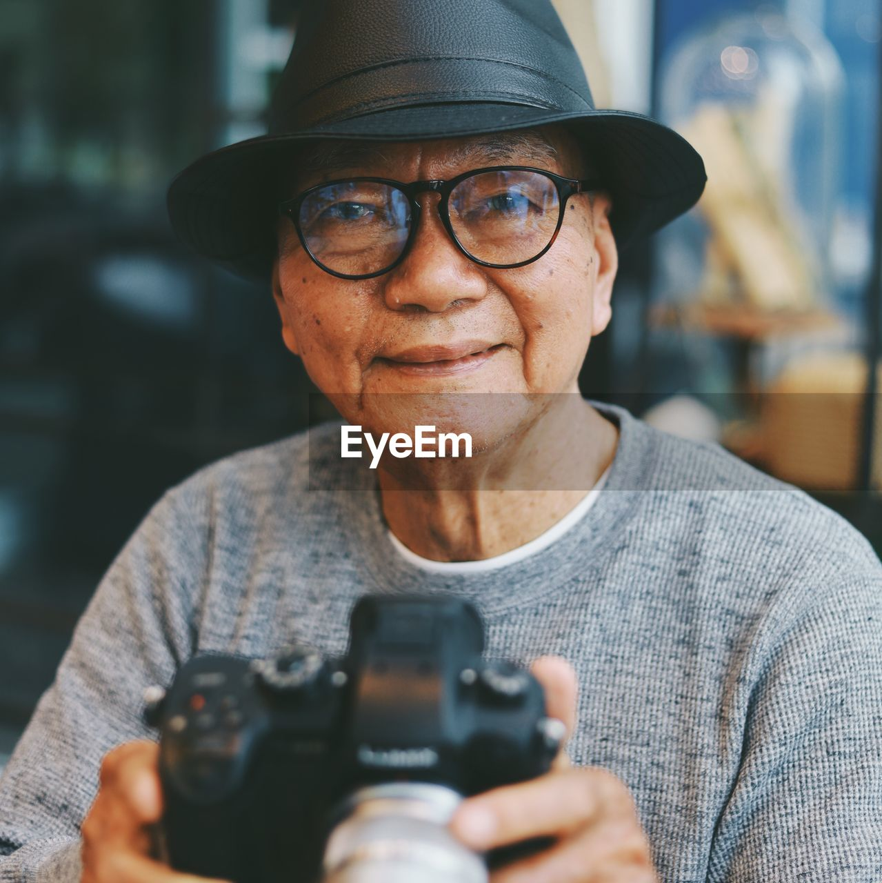 Portrait of senior man holding camera while sitting in cafe