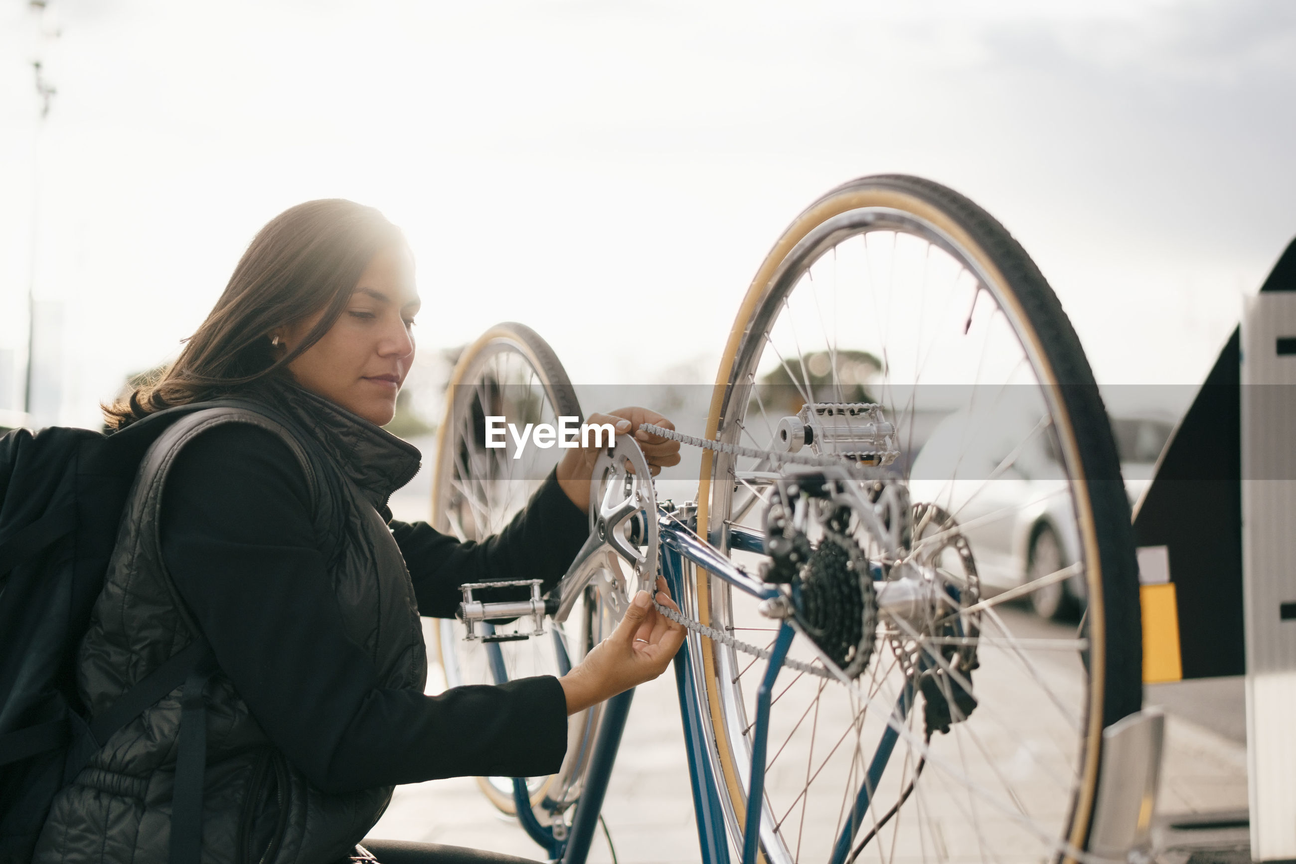 YOUNG WOMAN WITH BICYCLE STANDING ON THE ROAD